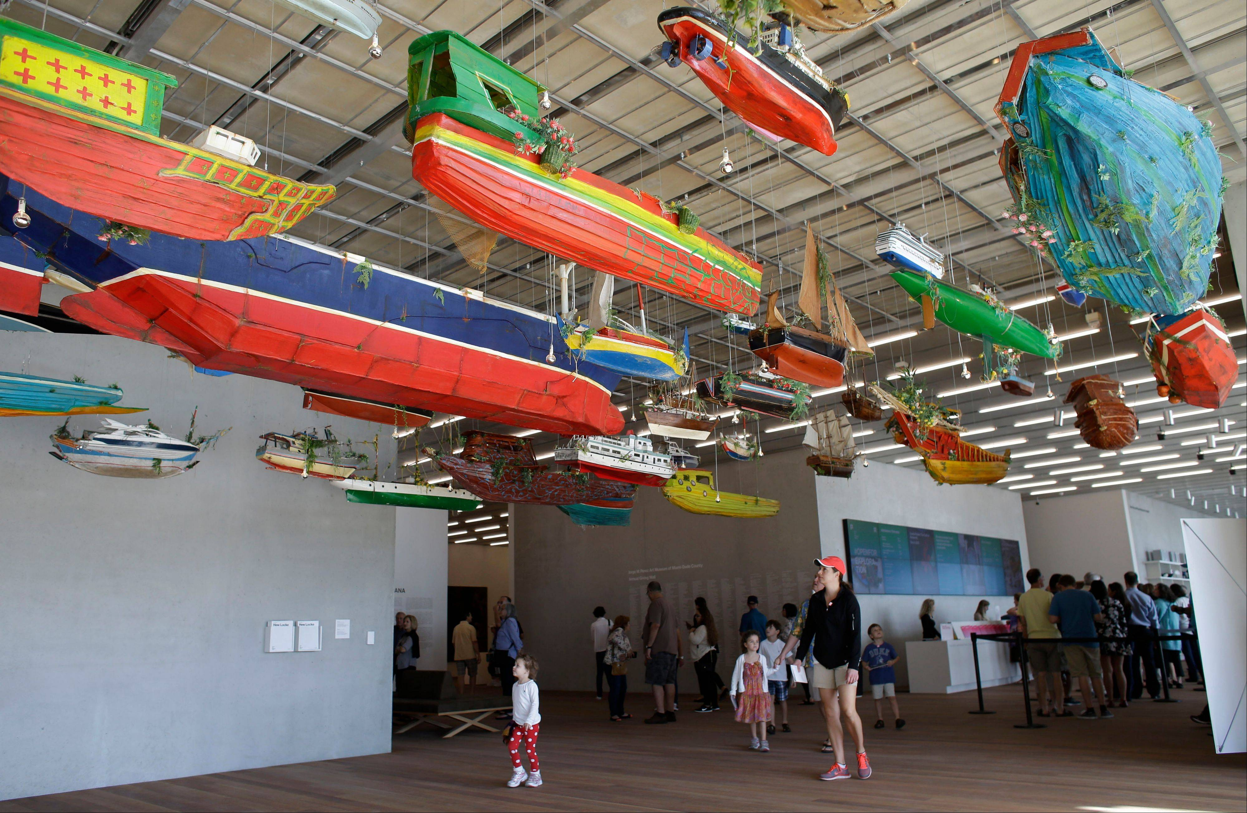 """For Those In Peril on the Sea"" by the Guyana-raised artist Hew Locke appears at the Perez Art Museum Miami, in Miami. The colorful display is both a playful nod to South Florida's maritime culture and a somber reference to those perilous journeys so many make to get there."