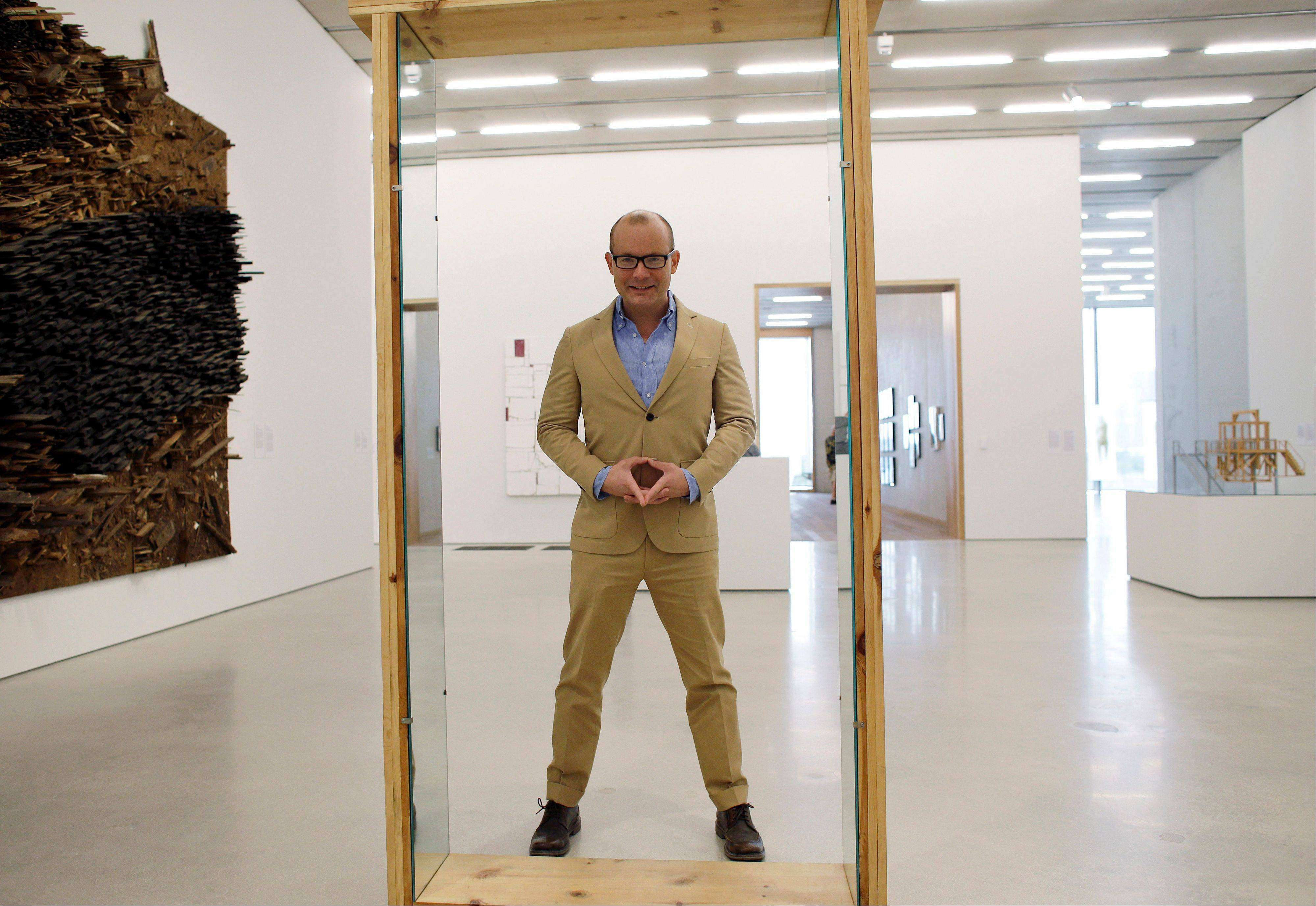 "Thom Collins, director of the Perez Art Museum Miami, stands by a piece by artist Robert Morris called ""Untitled (Pine Portal with Mirrors)"" in Miami. The museum, called the PAMM by locals, opened in December and is becoming a must-see destination for tourists and locals alike with its eclectic and provocative collection."