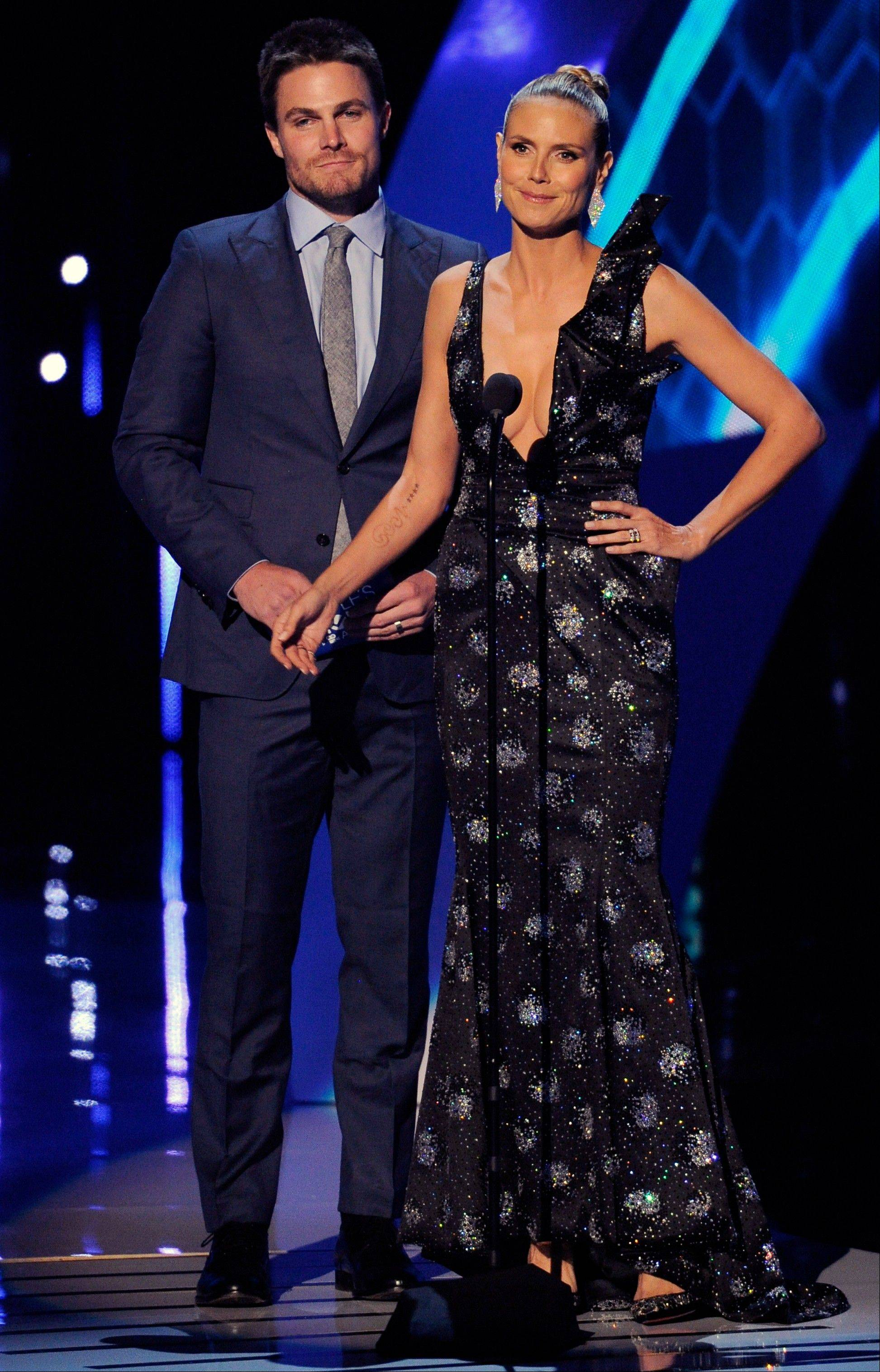 Associated PressStephen Amell, left, and Heidi Klum present the award for favorite pop artist at the 40th annual People's Choice Awards Wednesday in Los Angeles.