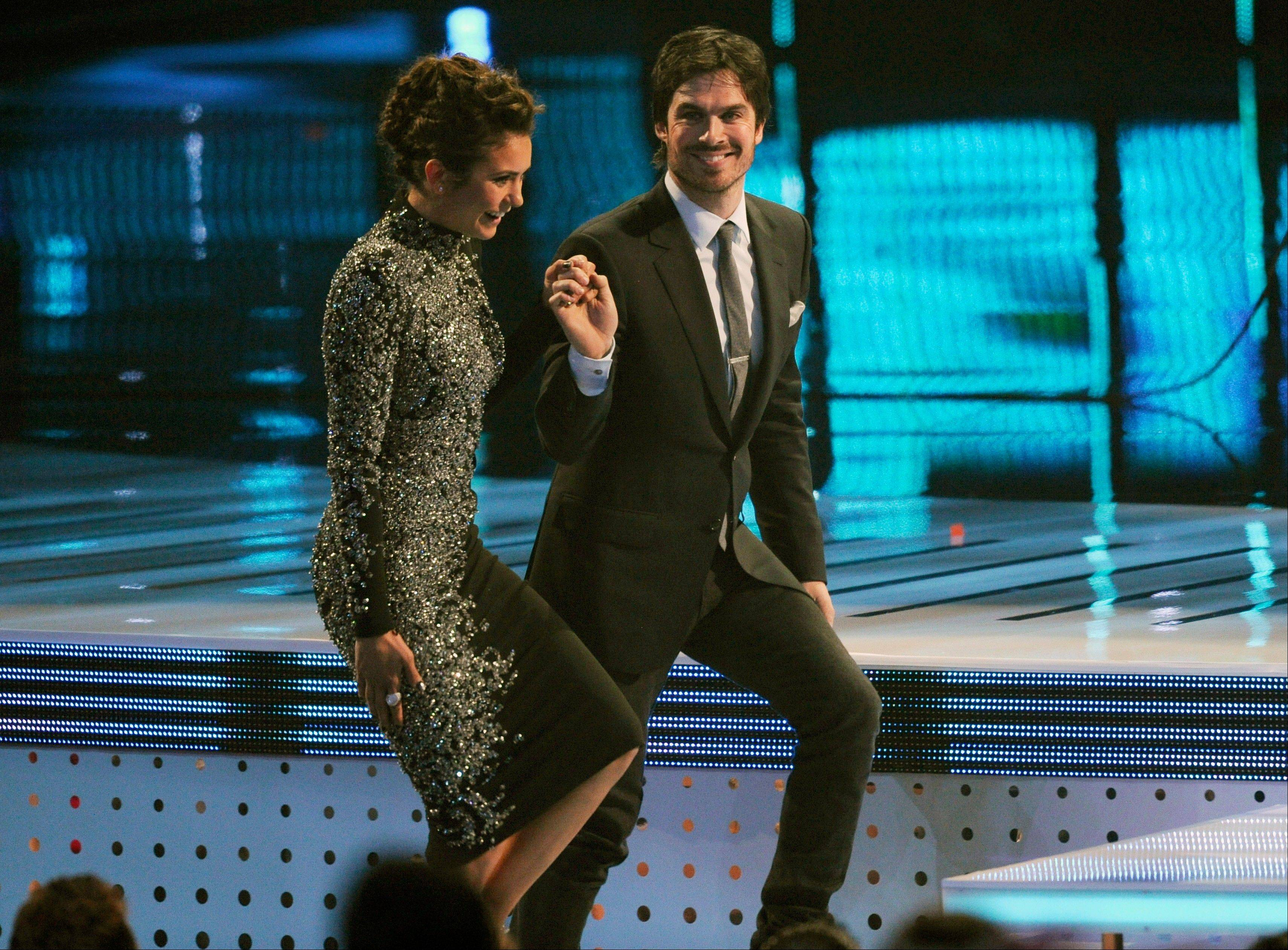 "Associated PressNina Dobrev, left, and Ian Somerhalder, winners of the award for favorite on-screen chemistry for ""The Vampire Diaries,"" walk on stage at the 40th annual People's Choice Awards Wednesday in Los Angeles."