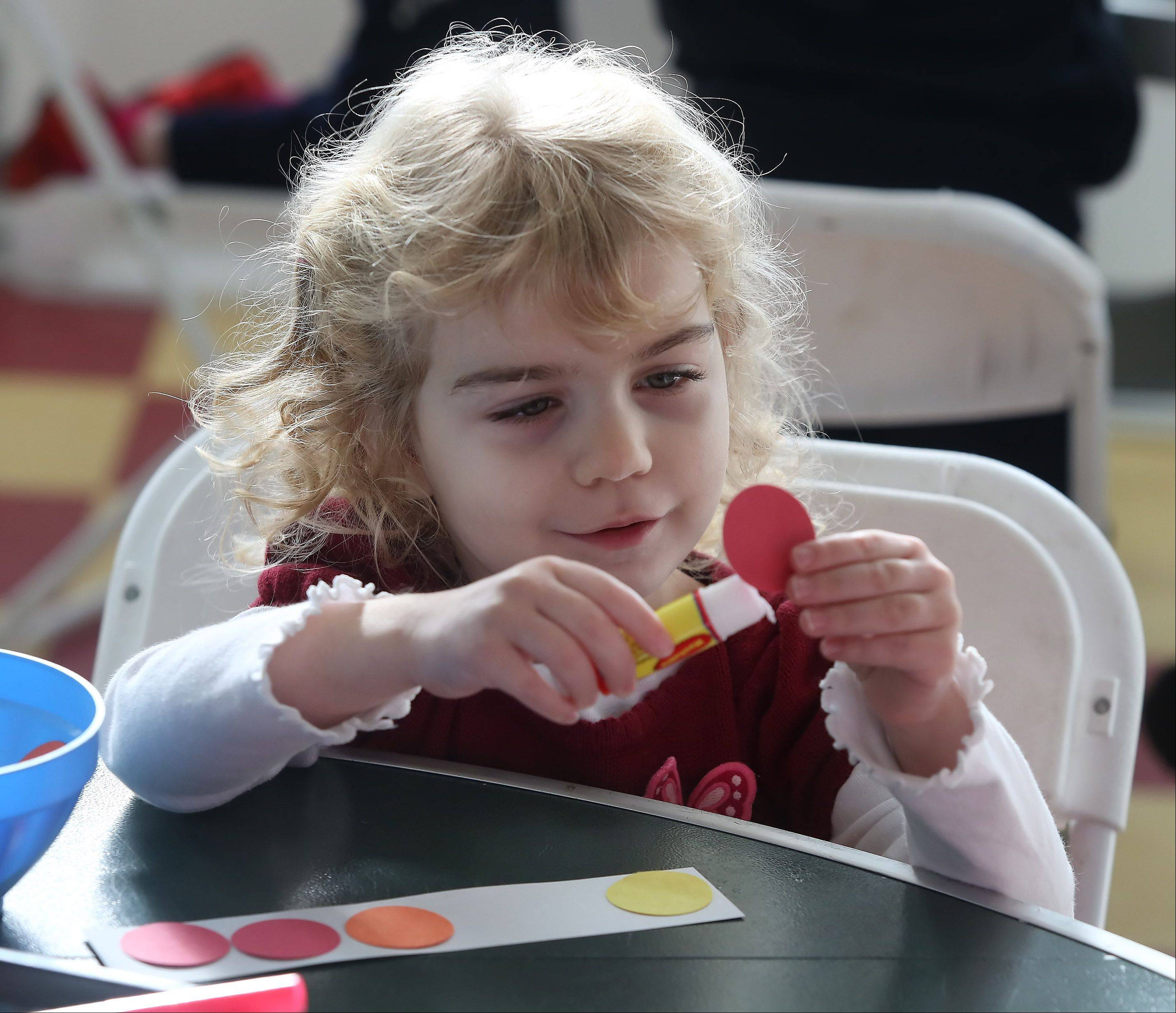 Stephanie Johnson, 4, of Lake Zurich, uses circle shapes to make a ladybug bookmark during the Colorful Creatures program Wednesday at the Lake County Discovery Museum near Wauconda. The Small Discoveries event focused on shapes and nature and coincided with the artwork exhibit of Charles Harper.