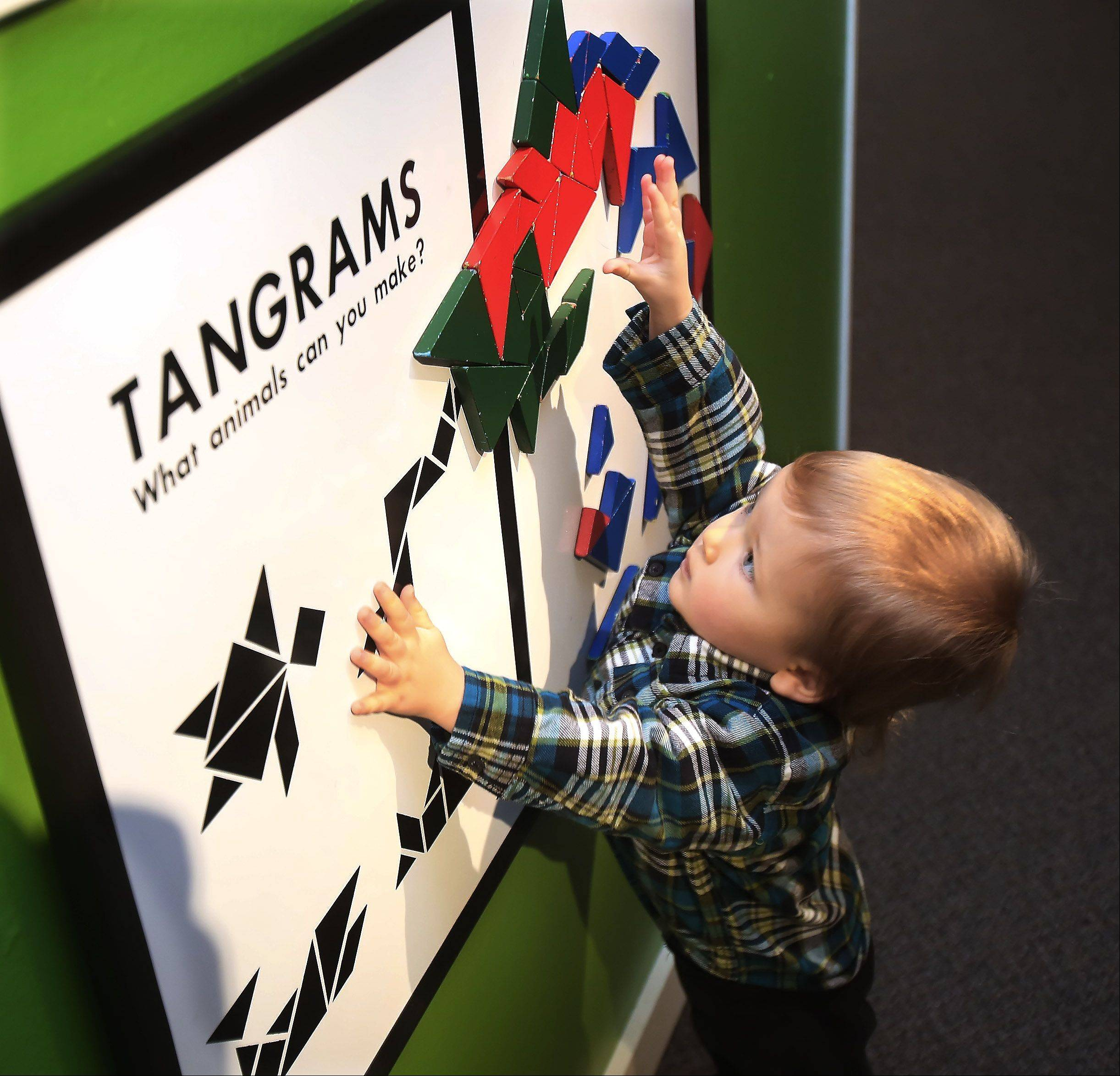 Leo Porten, 18-months-old, of Island Lake, plays with the tangrams board during the Colorful Creatures program Wednesday at the Lake County Discovery Museum near Wauconda. The Small Discoveries event focused on shapes and nature and coincided with the artwork exhibit of Charles Harper.