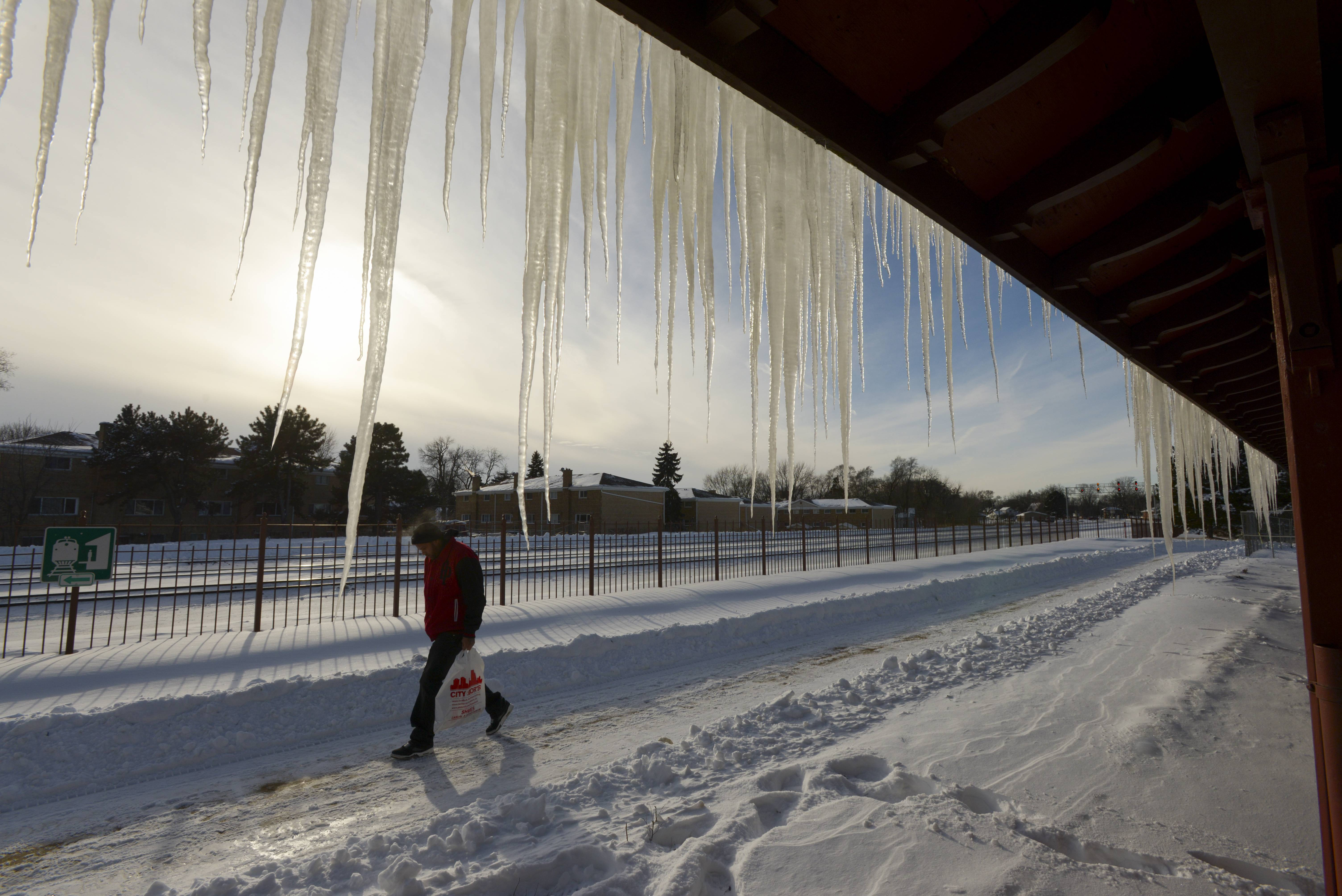 A pedestrian walks past the large Icicles hanging from the roof of the Wayne and Helen Fox Community Center in West Chicago.