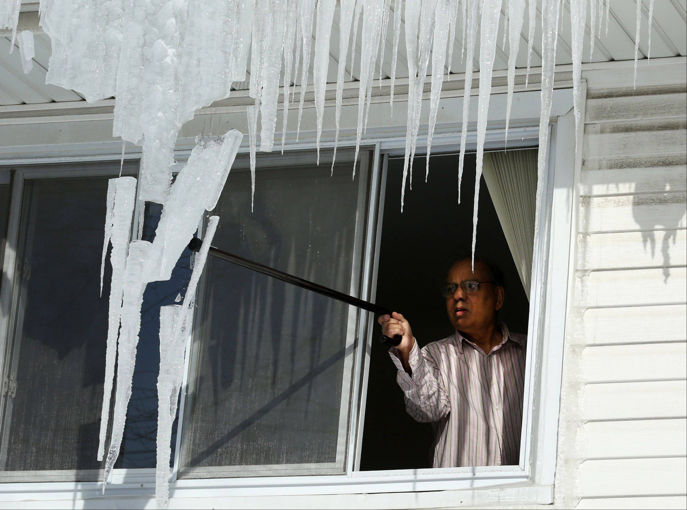 From a second-floor window, Mohammad Mohyuddin knocks icicles off of his home in Rolling Meadows using a walking cane on Wednesday.