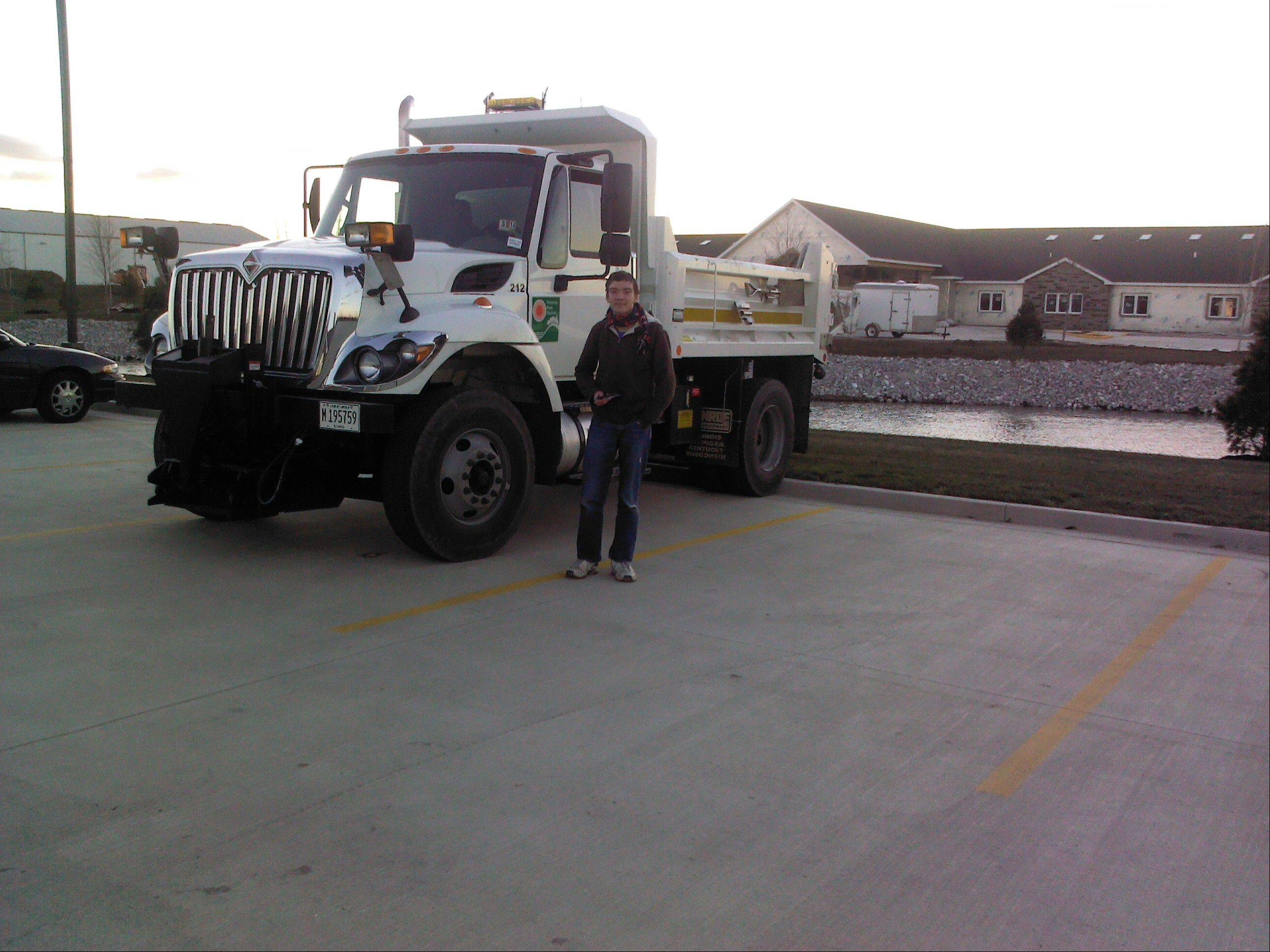 Ethan Davis stands with the Palatine Park District dump truck that was used in cleanup operations in Washington, Ill.