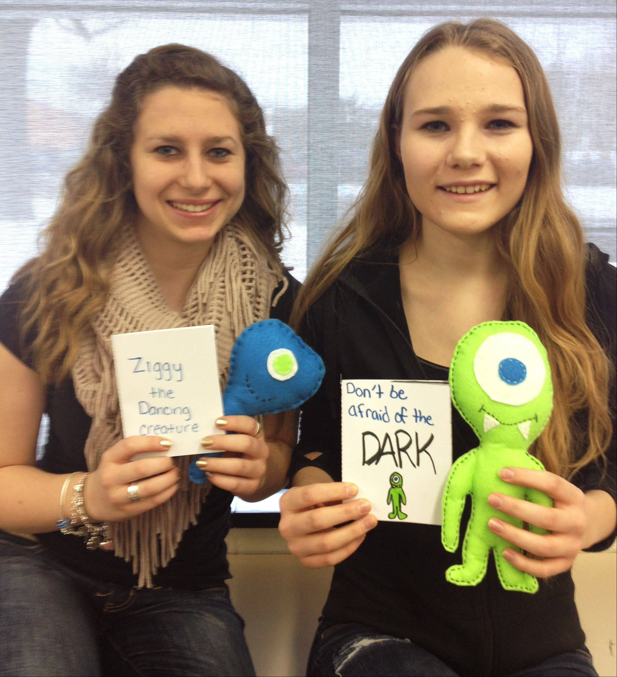 Mundelein High School students Anika Nawrot and Brianna Moehling display the Comfort Creature and story books. Students created their own product and storybook containing a unique story where the creature helps a child overcome a specific fear.