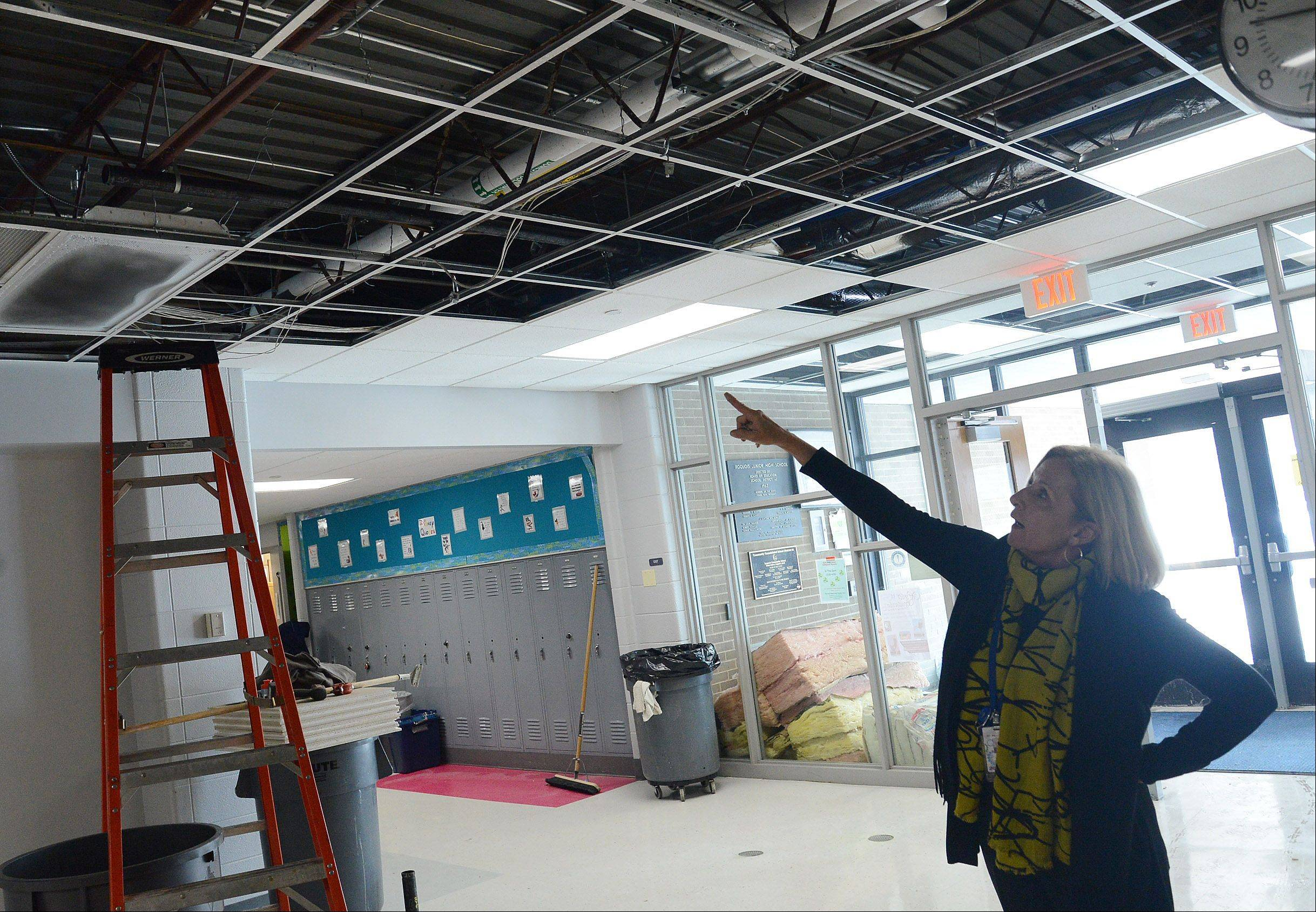 Des Plaines School District 62 Superintendent Jane Westerhold points to where a sprinkler system pipe burst earlier Wednesday at Iroquois Community School, forcing the abrupt cancellation of classes for the remainder of the day as well as Thursday. Officials blamed the pipe break on the recent spell of frigid weather.