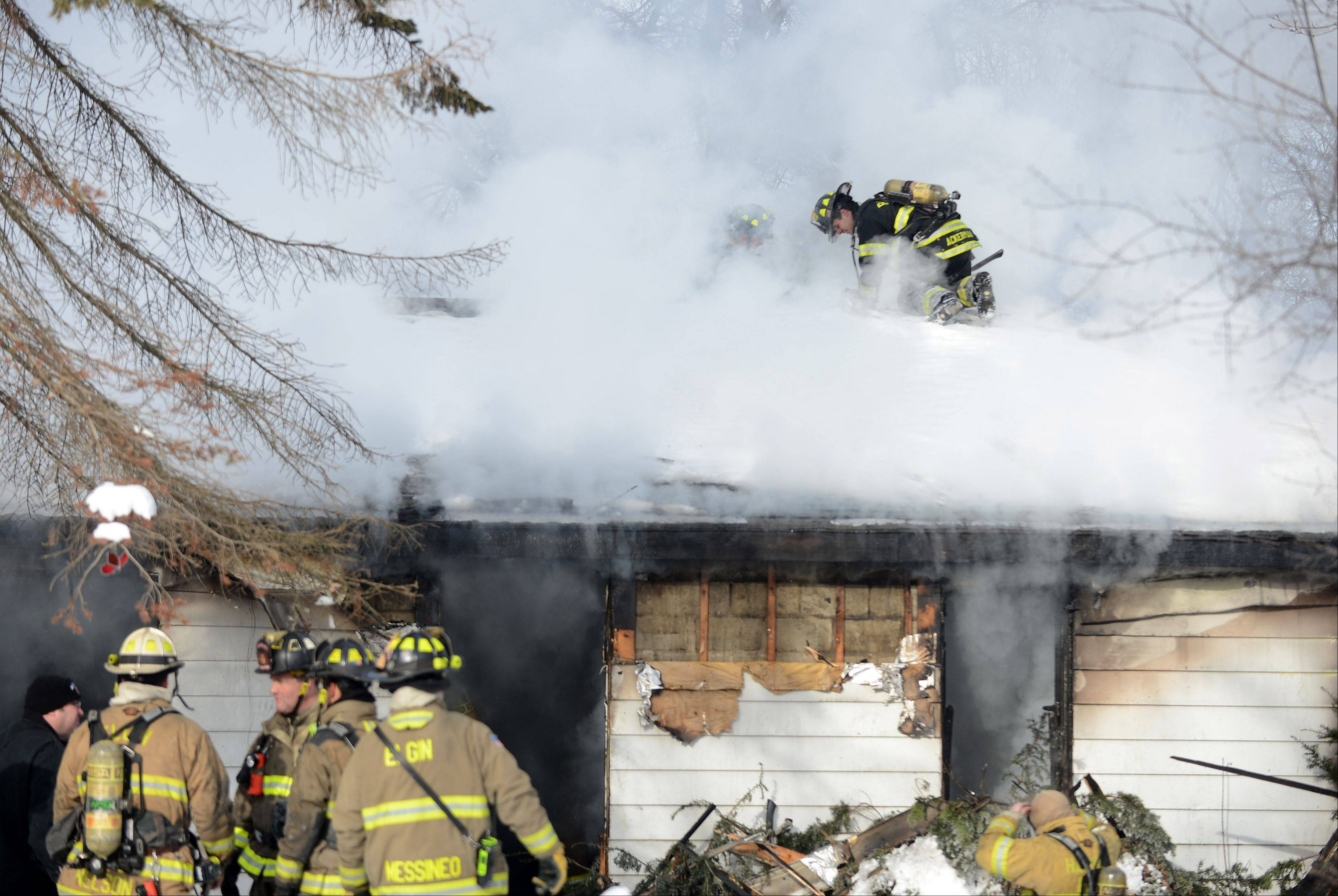 Firefighters from multiple departments work a fire Wednesday morning on the 100 block of Beck Avenue in South Elgin. A man and a dog died in the fire while the man's wife and another dog were saved.