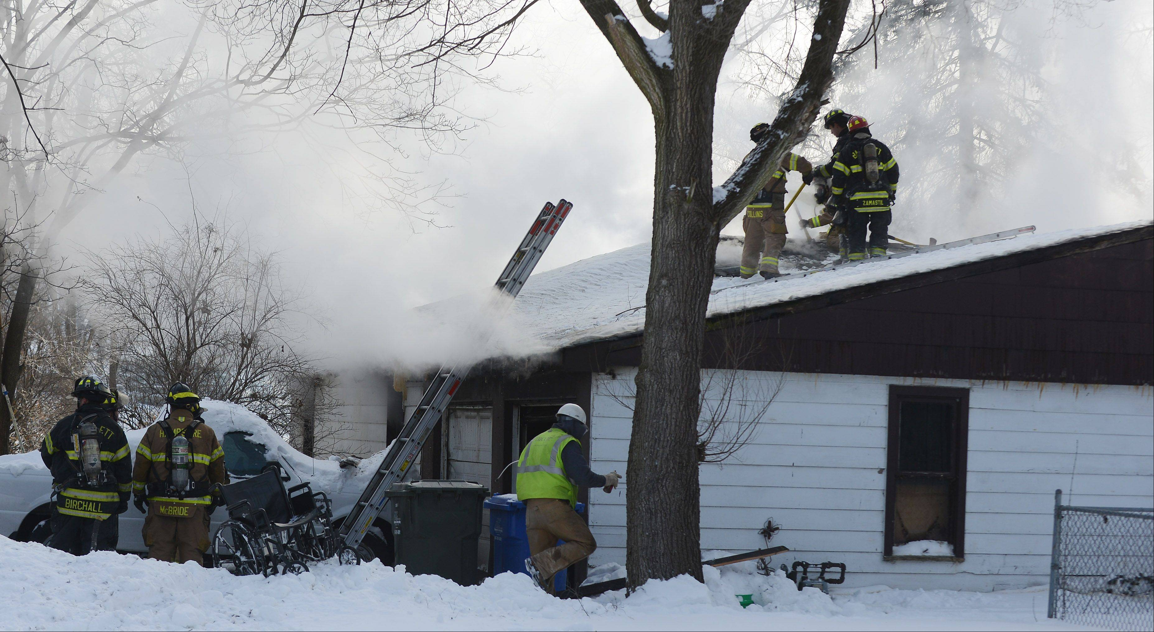 Firefighters from multiple departments work a fire Wednesday on the 100 block of Beck Avenue in South Elgin. One man and a dog died in the fire while the man's wife and another dog were saved.