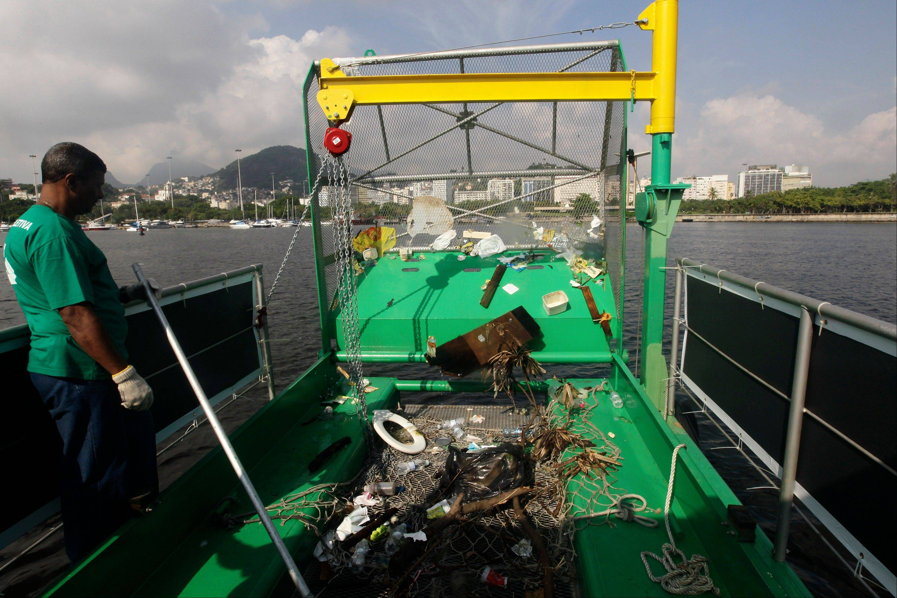 A worker stands next to trash collected by a garbage-collecting barge at the Guanabara Bay, in Rio de Janeiro, Brazil.