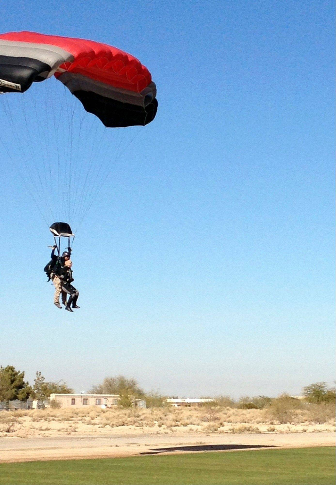 Former U.S. Rep. Gabrielle Giffords, right, comes in for a landing during a tandem sky-dive Wednesday, Jan. 8, 2014, in Tucson, Ariz. Giffords, severely injured three years ago in a mass shooting, marked the anniversary by sky diving for a report and interview for NBC�s �Today� show.