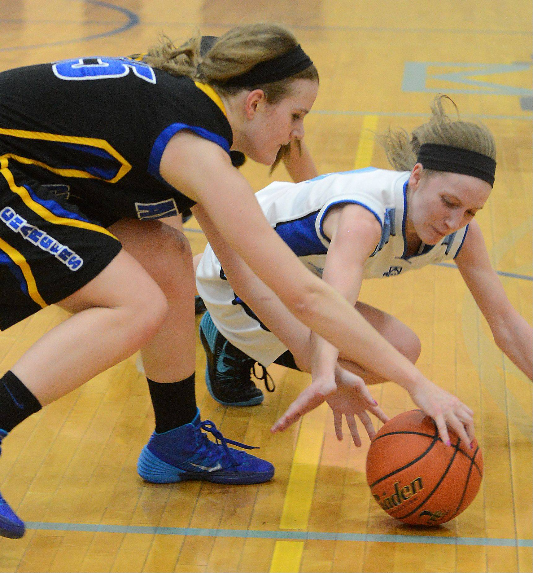 Aurora Central Catholic�s Natalie Droeske (15) and Rosary�s Rachel Choice (3) battle for a loose ball during Thursday�s game at Rosary.