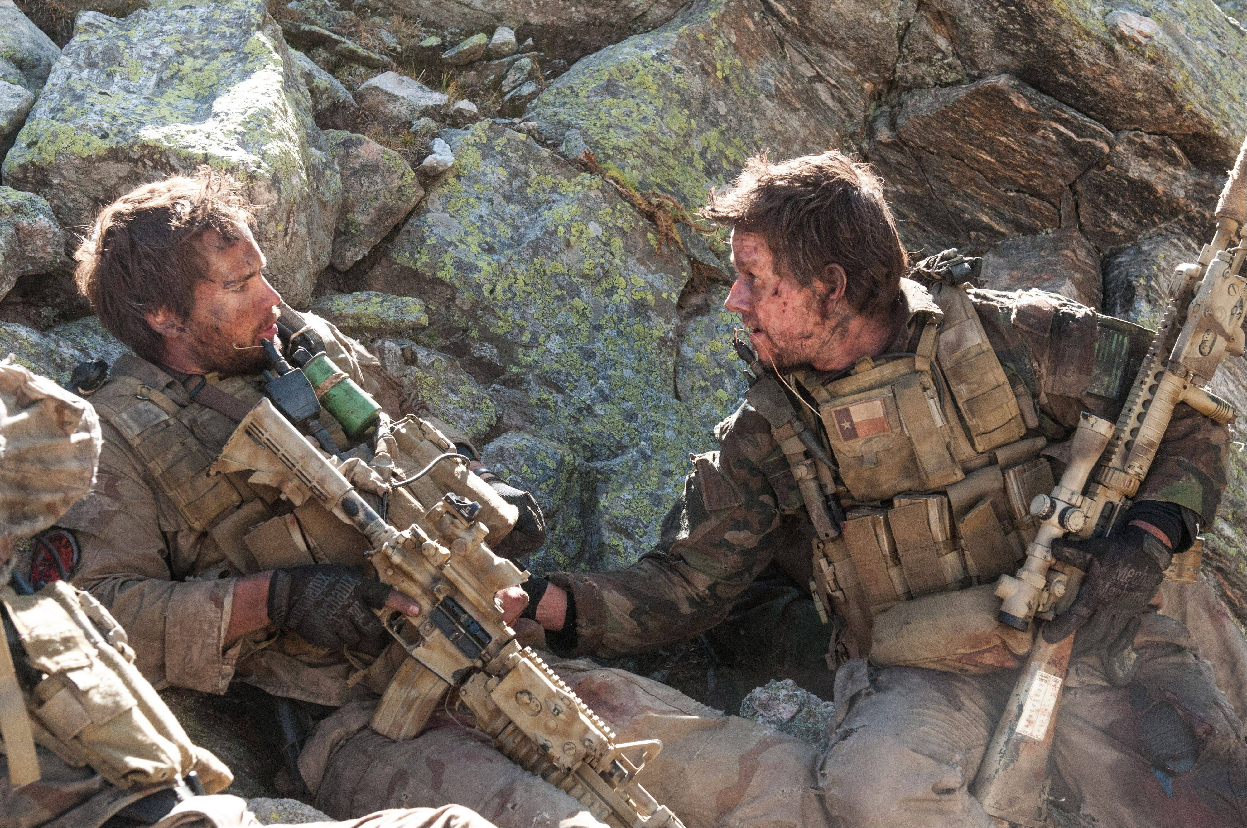 "Lt. Murphy (Taylor Kitsch), left, and Marcus Luttrell (Mark Wahlberg) take stock of their situation in Peter Berg's fact-based drama ""Lone Survivor."""