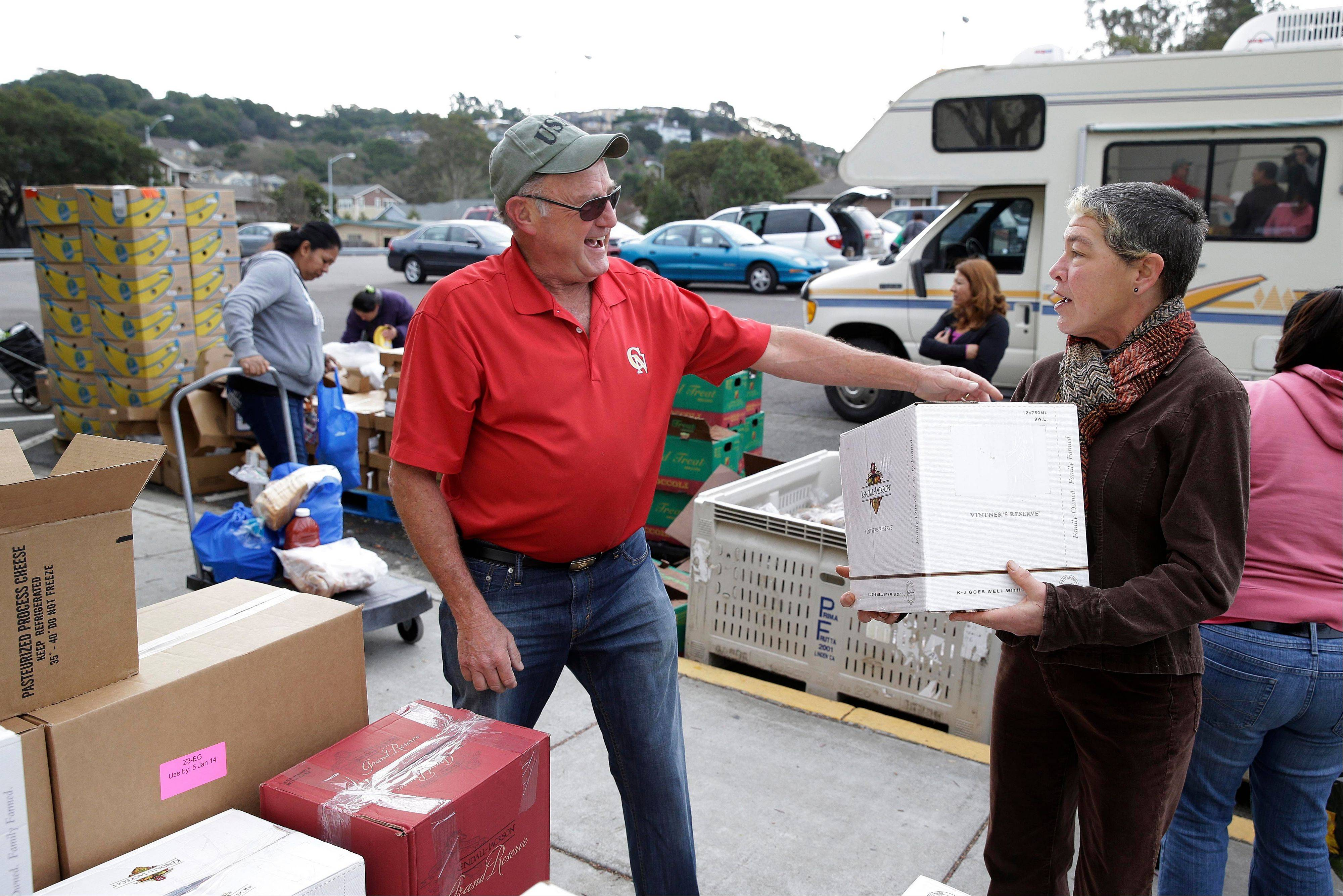 Steve Bosshard, center, distributes a specially prepared box of food at a food bank distribution Wednesday in Petaluma, Calif., as part of a research project with Feeding America to try to improve the health of diabetics in food-insecure families.