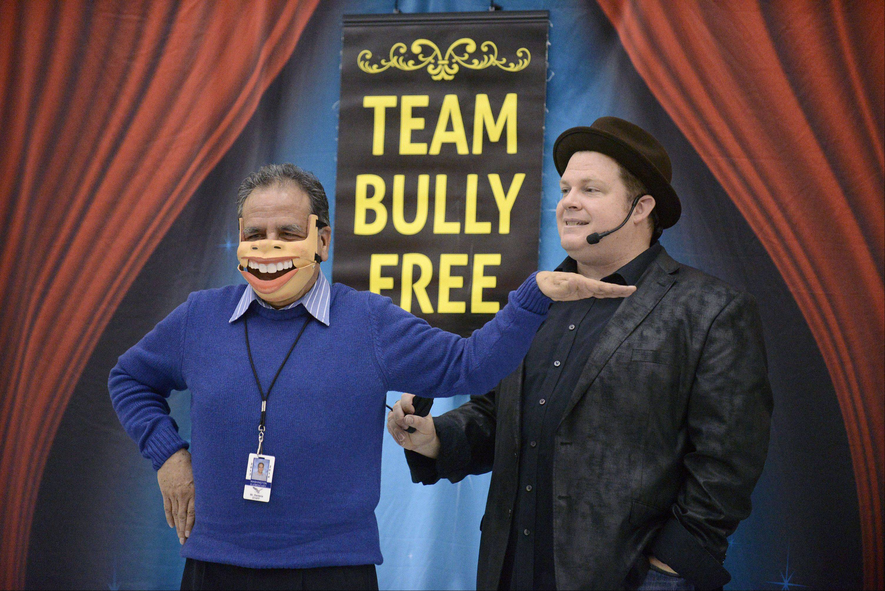 "Third-grade teacher Miguel Renteria acts as a puppet by singing ""I'm a little teacup, short and stout,"" as performer/ventriloquist Chris McBrien of Lisle controls a moving mouth mask during his ""Team Bully Free"" program Thursday at Washington Elementary School in Elgin. This demonstration taught kids the difference between laughing at someone and laughing with someone, as well as never allowing anyone to speak for you. Renteria was a good sport and laughed behind the mask along the way."