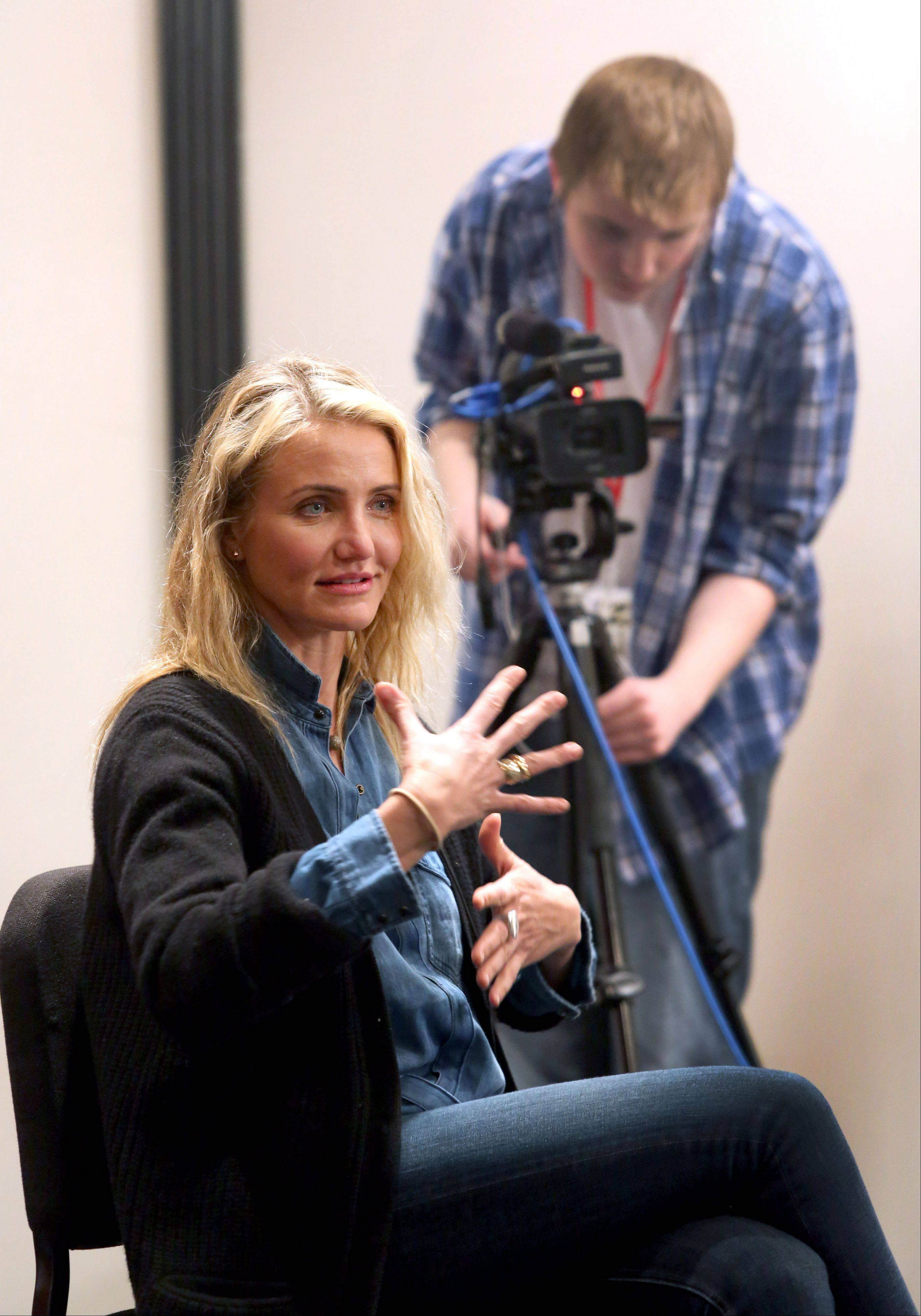 "Patrick Oberle, a junior at Neuqua Valley High School in Naperville, works the camera Thursday as actress Cameron Diaz is interviewed by students in a media production class before speaking about her new book ""The Body Book: The Law of Hunger, the Science of Strength and Other Ways to Love Your Amazing Body."""