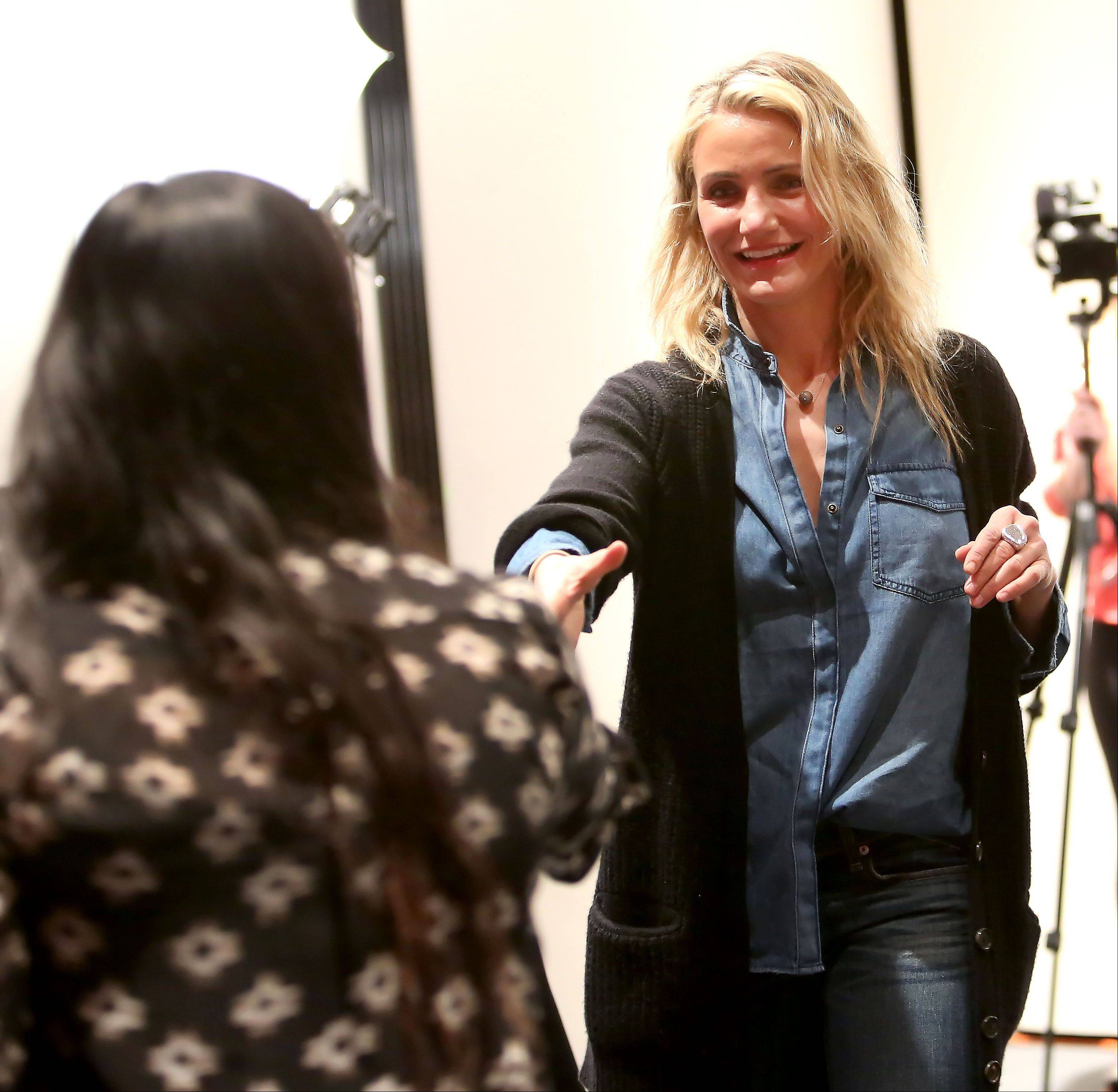 "Actress Cameron Diaz greets Neuqua Valley High School senior and ""The Echo"" newspaper staffer Sara Saggar before speaking to students Thursday about her new book, ""The Body Book: The Law of Hunger, the Science of Strength and Other Ways to Love Your Amazing Body."""