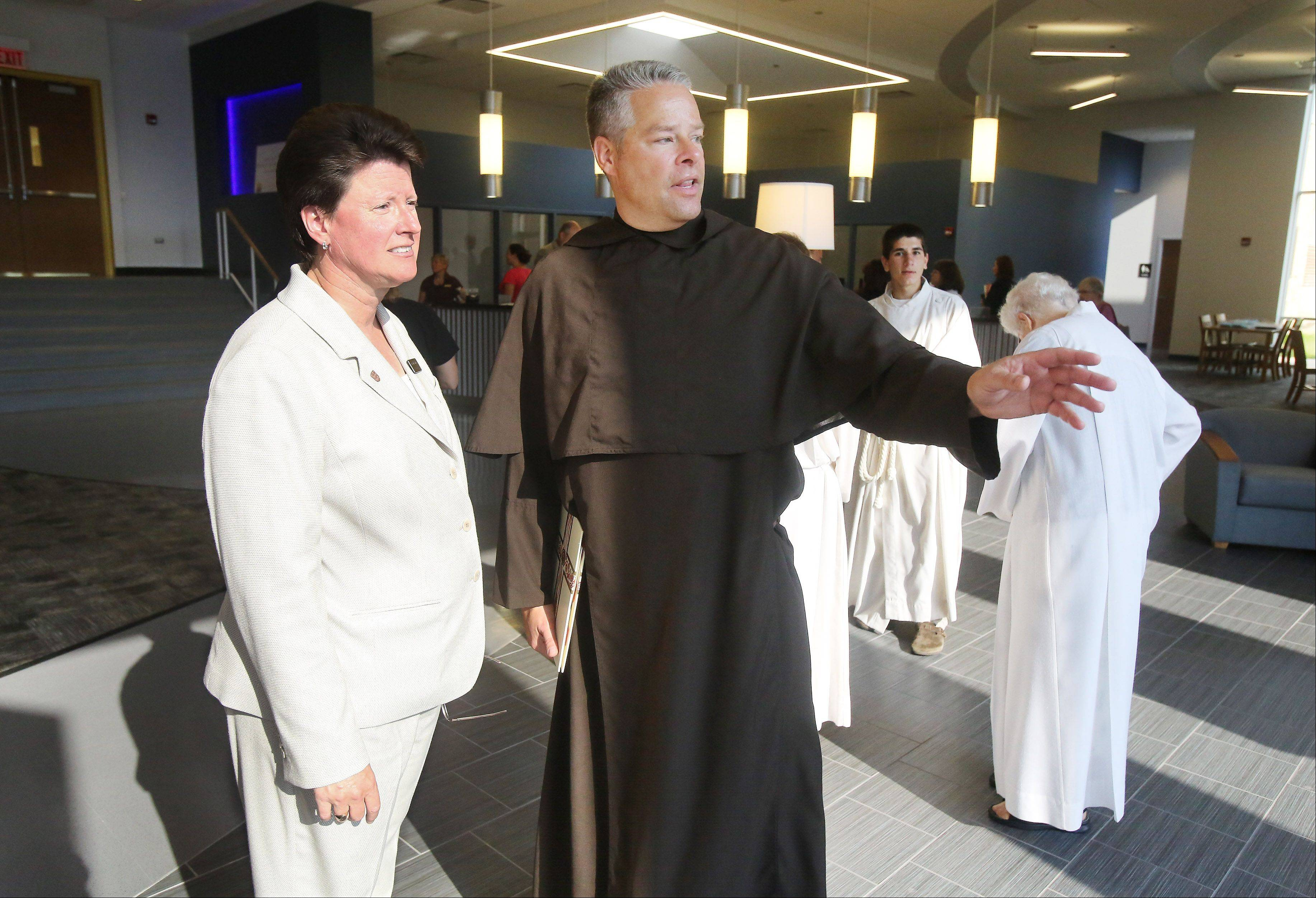 Carmel High School President Judith Mucheck, left, talks with the Rev. Carl Markelz during the dedication ceremony for the Fine and Performing Arts Center and Information Commons at the school in Mundelein. Mucheck resigned as president effective Jan. 3, the school announced Thursday.