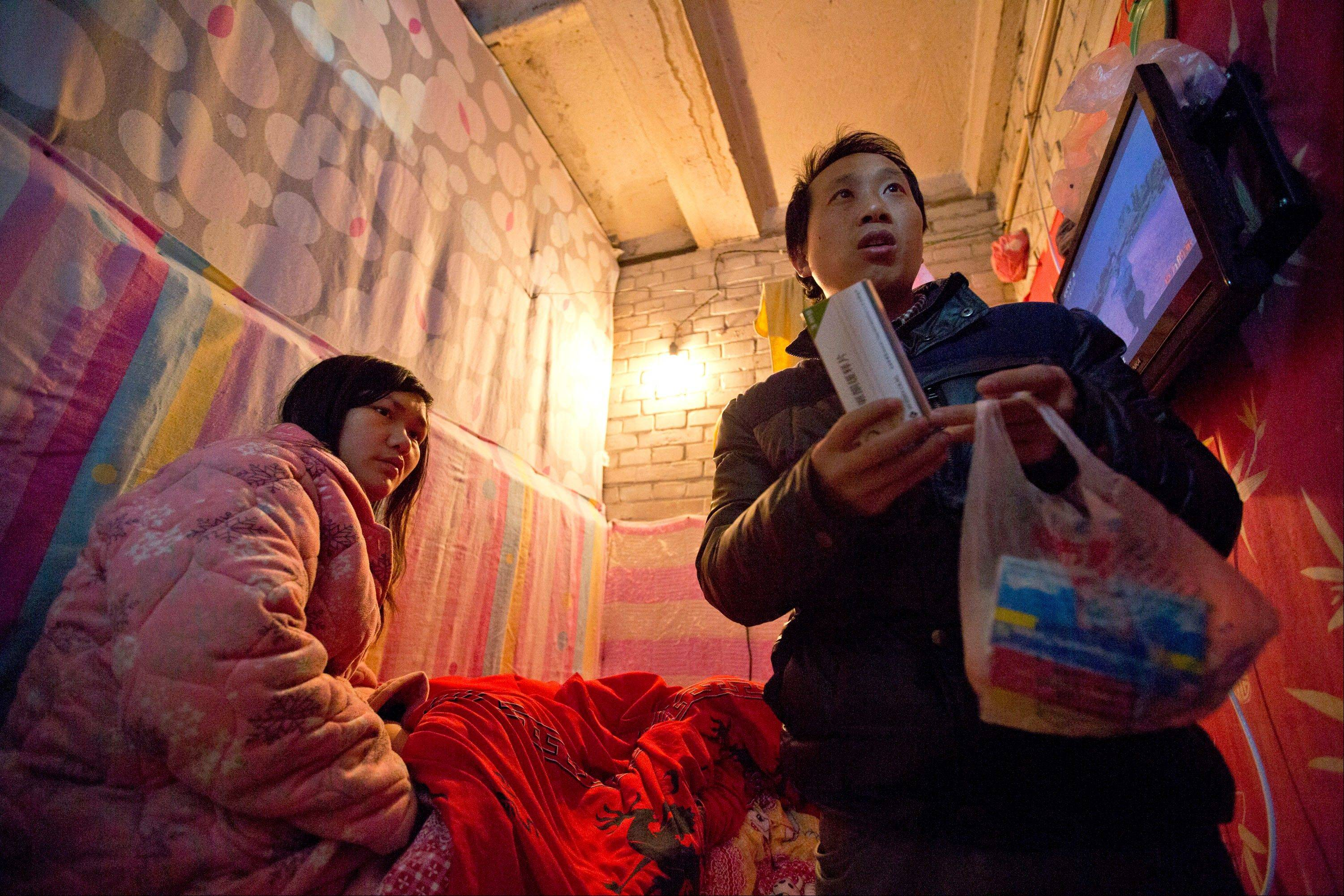 Wu Yongyuan, right, shows medicines his wife Gong Qifeng, left, takes to control her schizophrenia symptoms. When Gong's mind is clear, she can recall how she begged for mercy as several people pinned her down and drove a syringe of labor-inducing drugs into her stomach when she was seven months pregnant.
