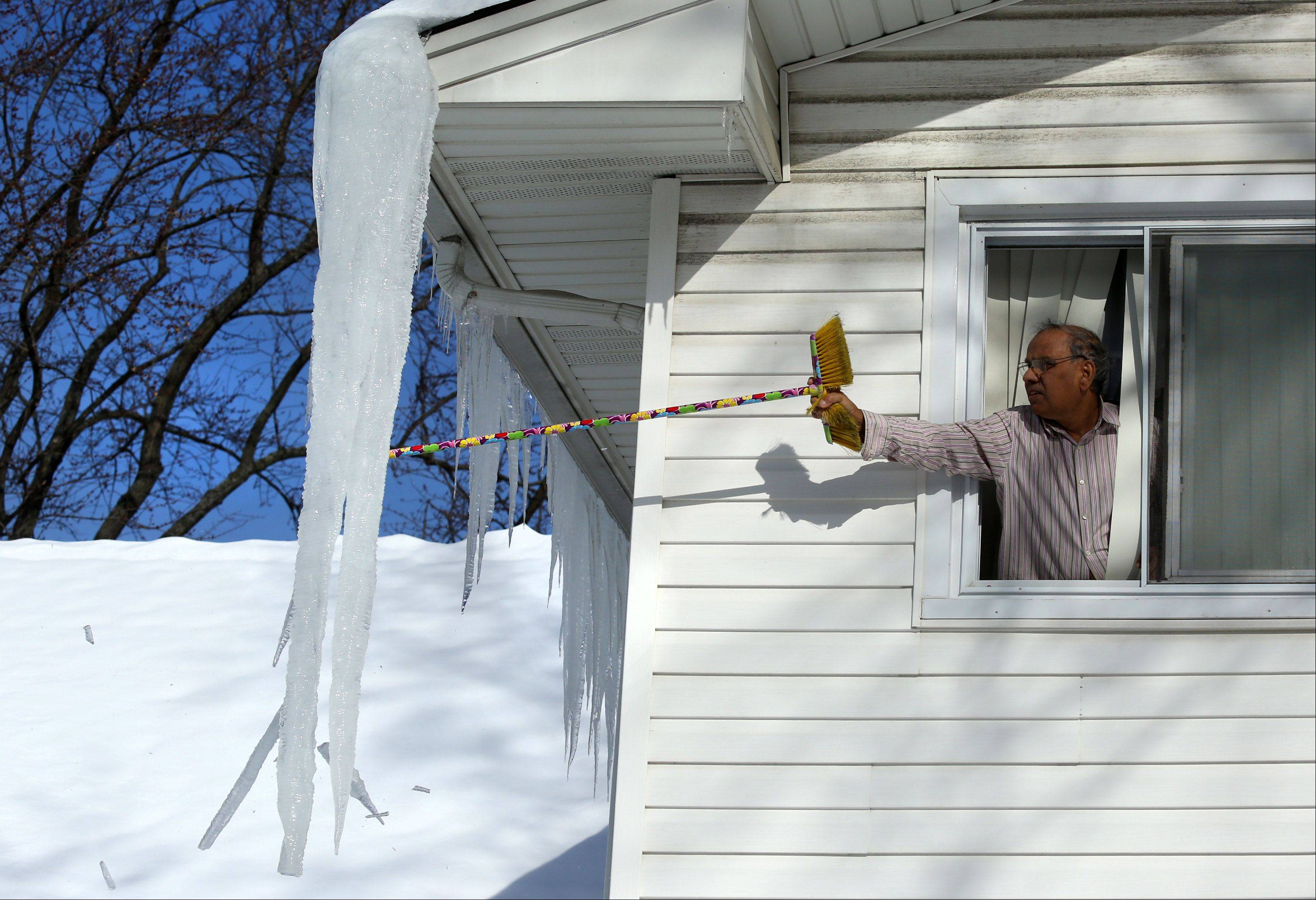 Leaning out a second-floor window, Mohammad Mohyuddin finds a broom a little too short to knock icicles off his home in Rolling Meadows.
