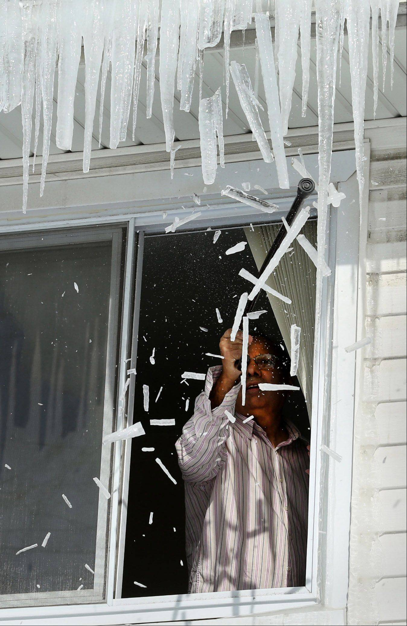 Eager to remove icicles from his Rolling Meadows home, Mohammad Mohyuddin knocks them off with a walking cane on Wednesday. Experts are divided on whether icicles need to go.