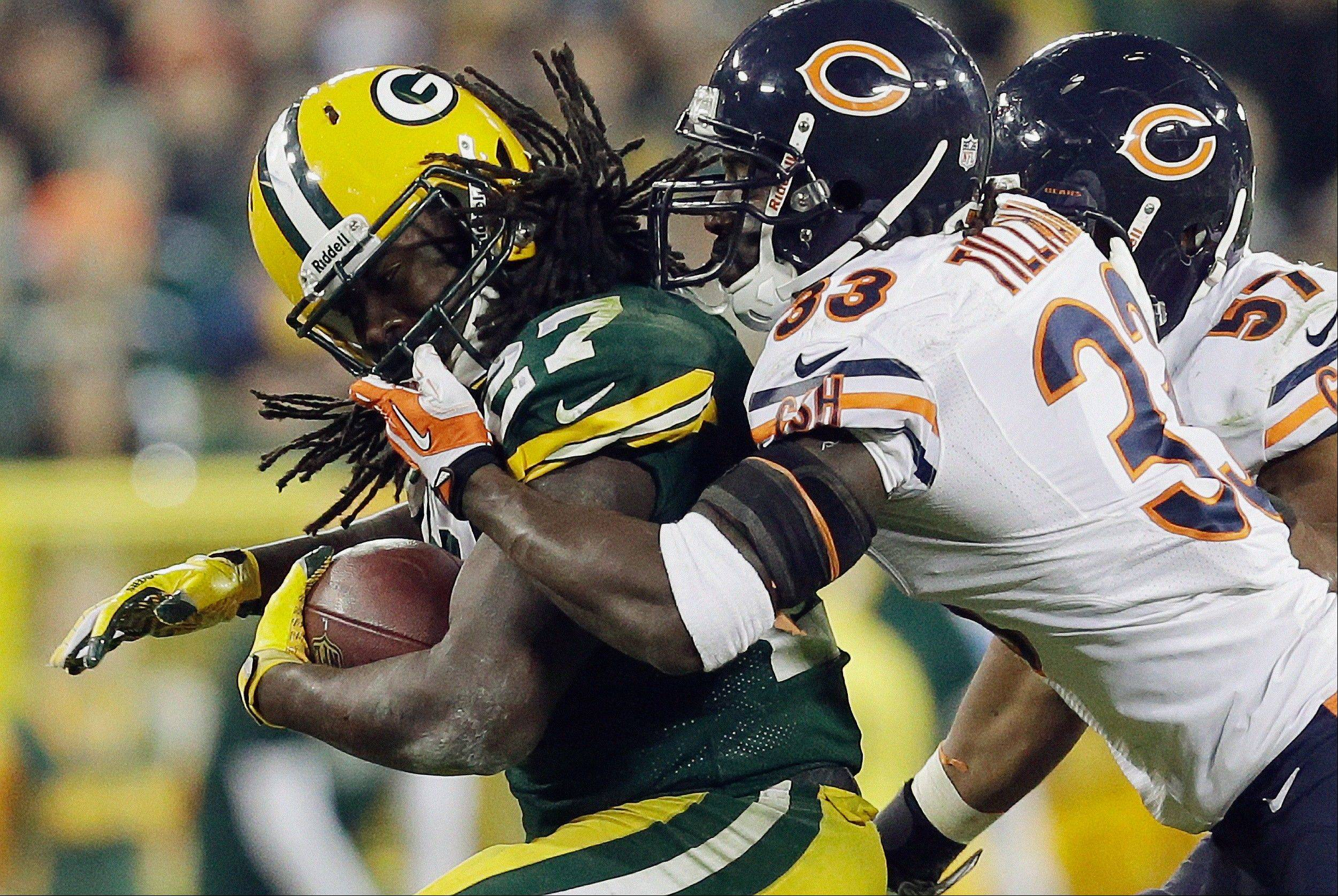 Charles Tillman (33) grabs the face mask of Green Bay Packers' Eddie Lacy during the second half of an NFL football game Monday, Nov. 4, 2013, in Green Bay, Wis. The Bears won 27-20.