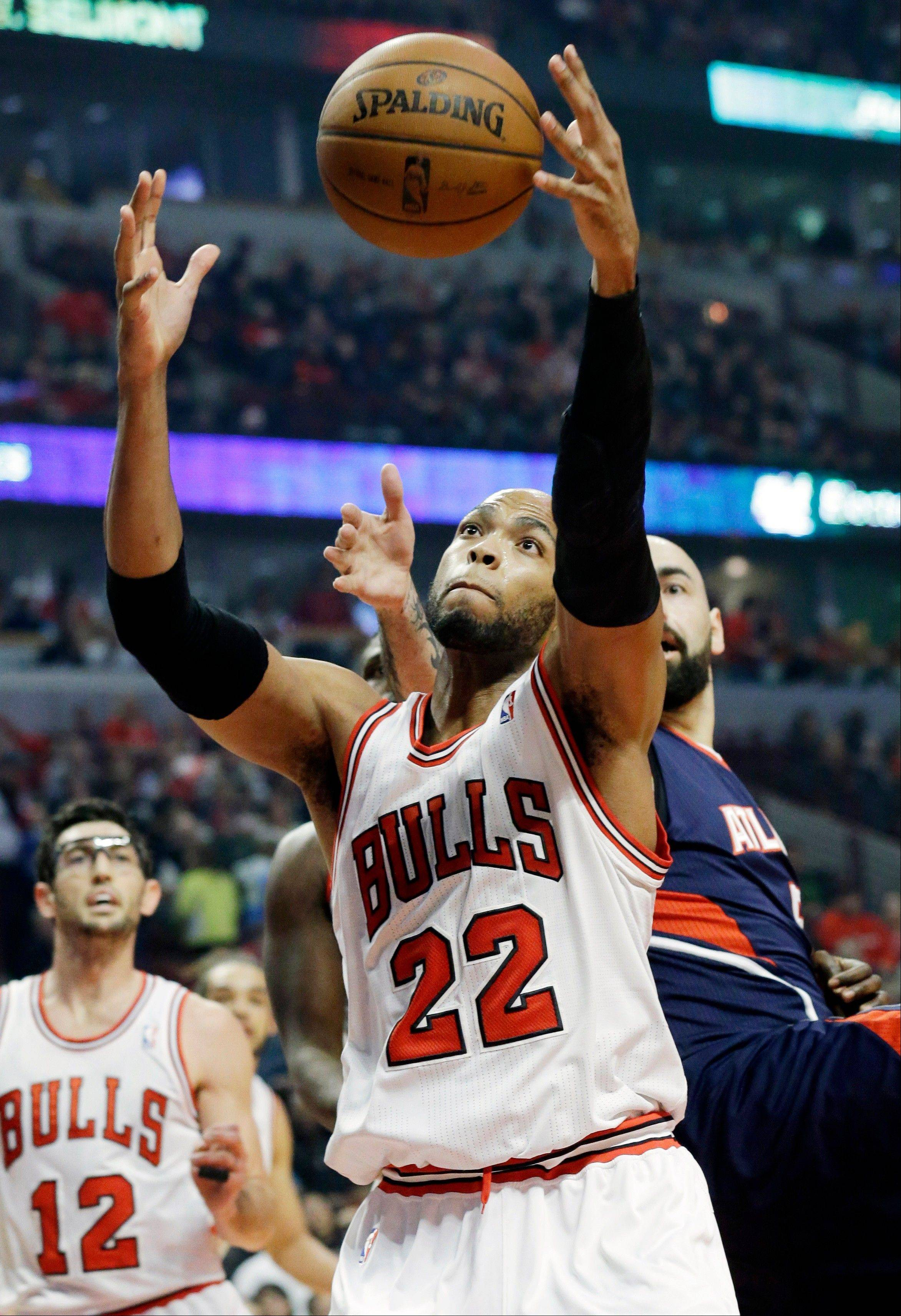 Bulls forward Taj Gibson (22) rebounds the ball against Atlanta Hawks center Pero Antic during the first half of an NBA basketball game in Chicago on Saturday, Jan. 4, 2014.