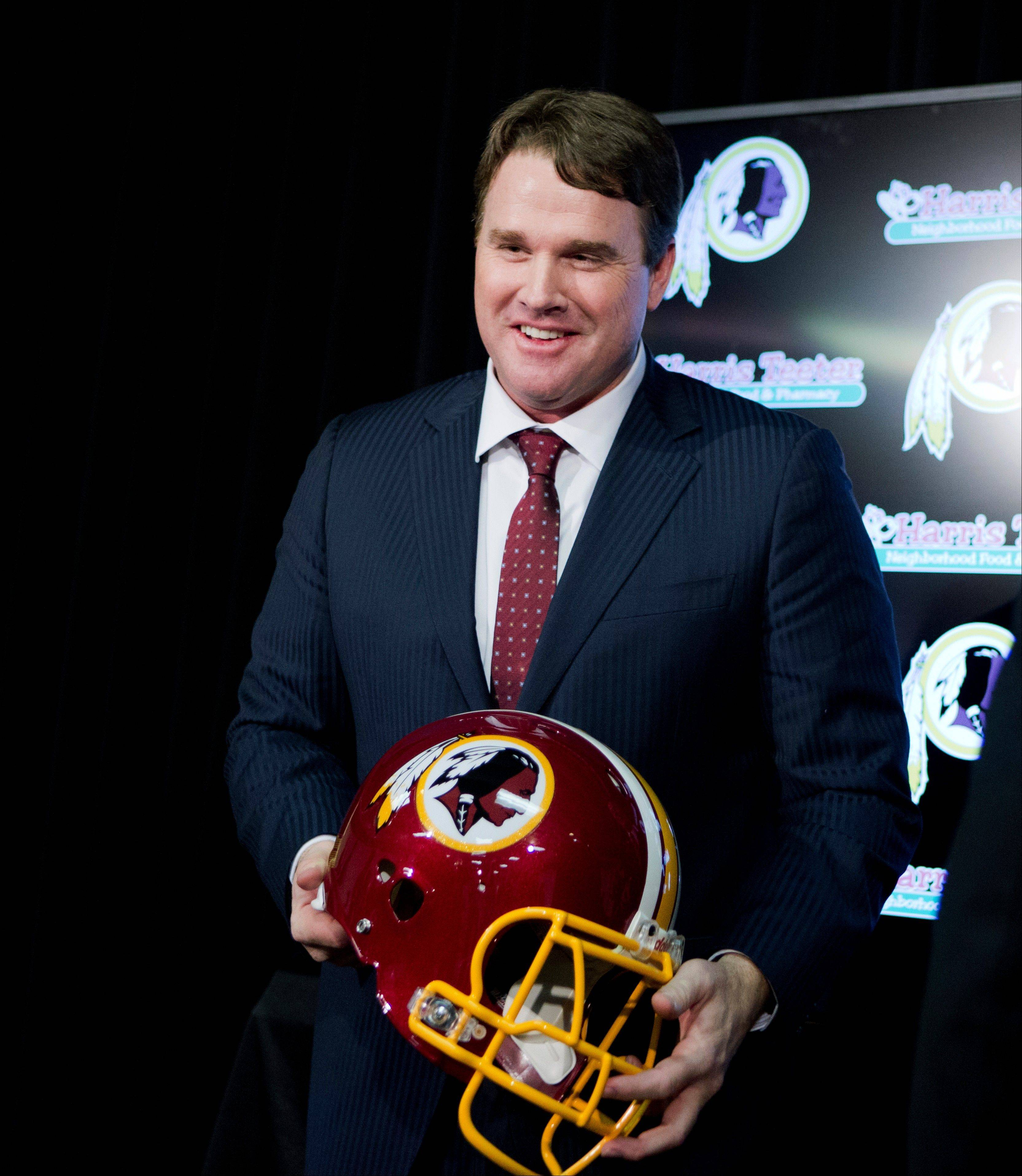New Washington Redskins head coach Jay Gruden, holds a Redskins helmet at the Redskins Park in Ashburn, Va., Thursday, Jan. 9, 2014. Jay Gruden was introduced as the new Washington Redskins head coach, replacing Mike Shanahan and becoming the teamís eighth head coach since Daniel Snyder purchased the franchise in 1999.