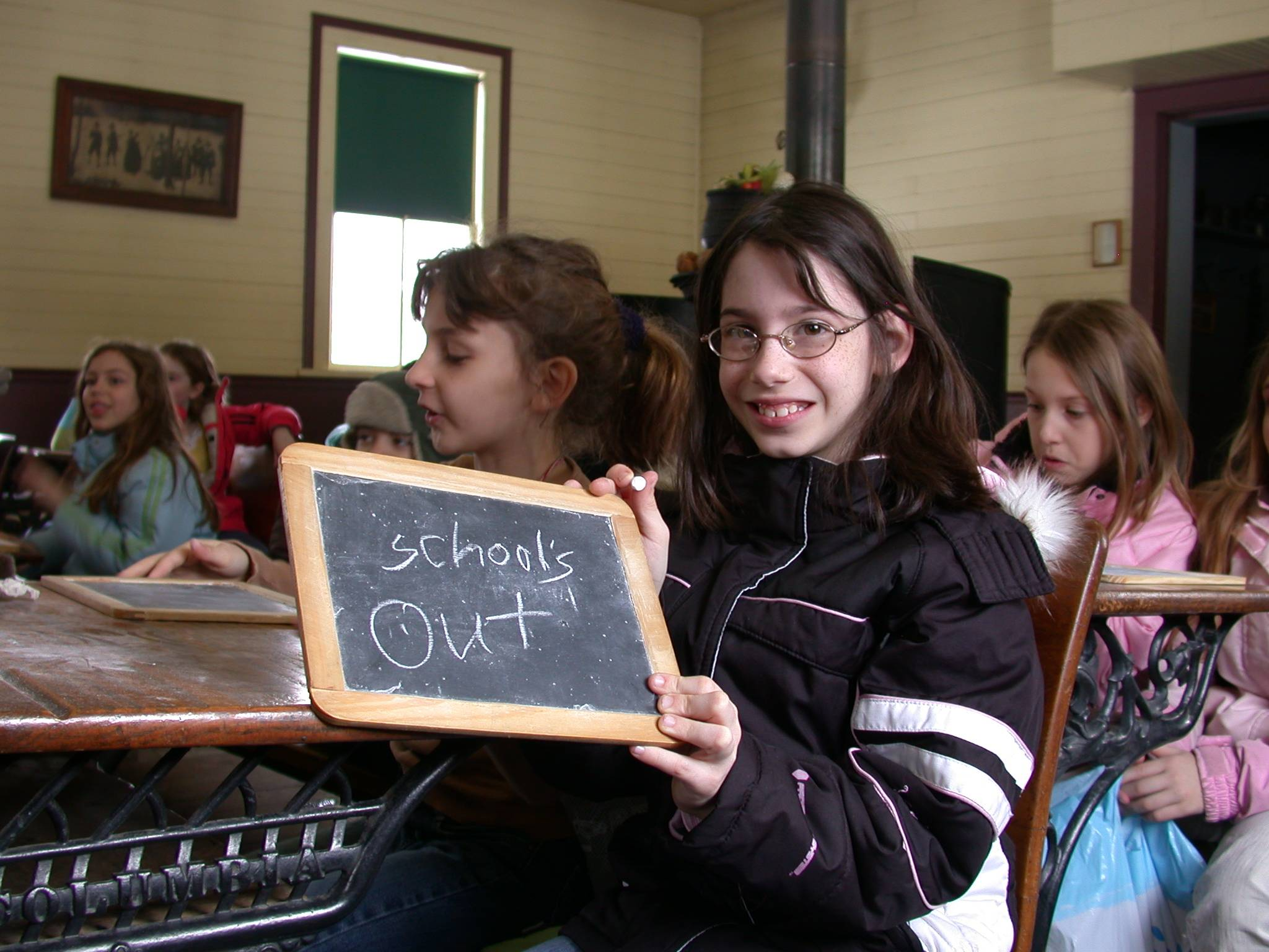 During School's Out: Book It!, students in grades 1-5 can visit Naper Settlement's one-room schoolhouse to recite a poem and write on a slate.