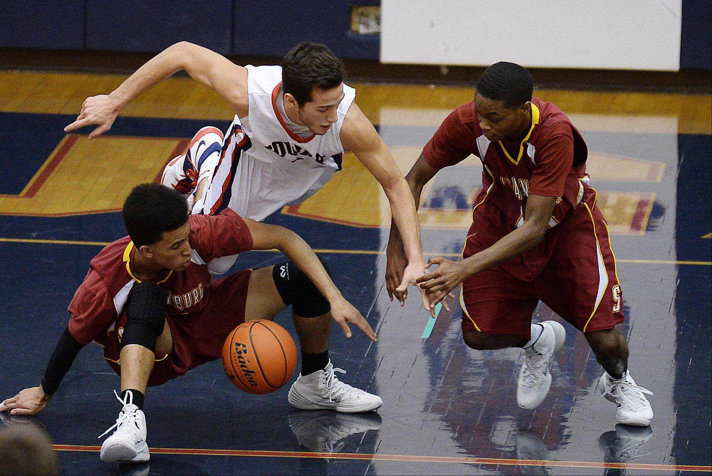 Conant�s Joe Ranallo goes after a loose ball with Schaumburg�s Brendan Parker and Marquis Woodard.