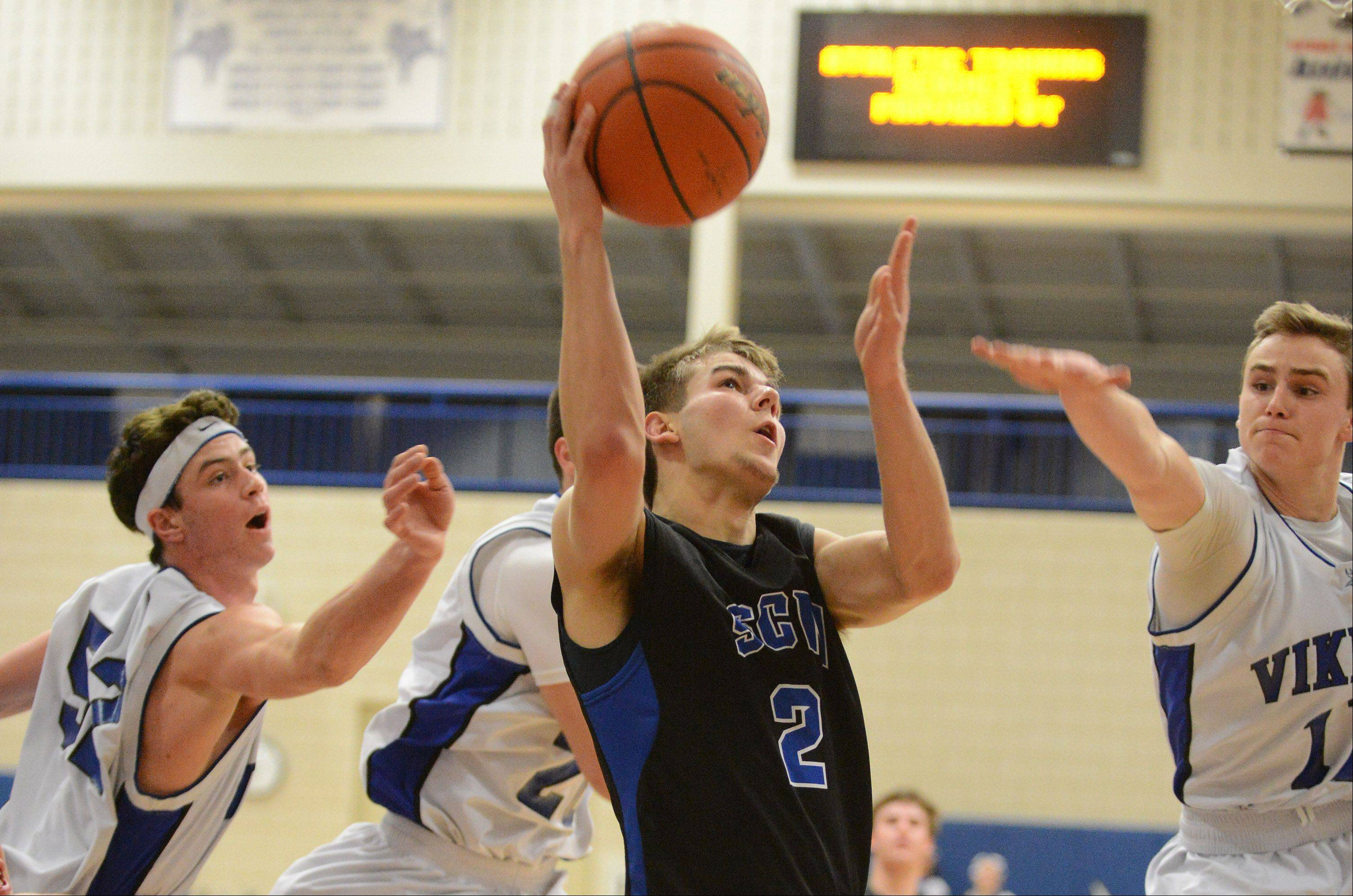 St. Charles North�s Jake Ludwig splits a trio of Geneva defenders.