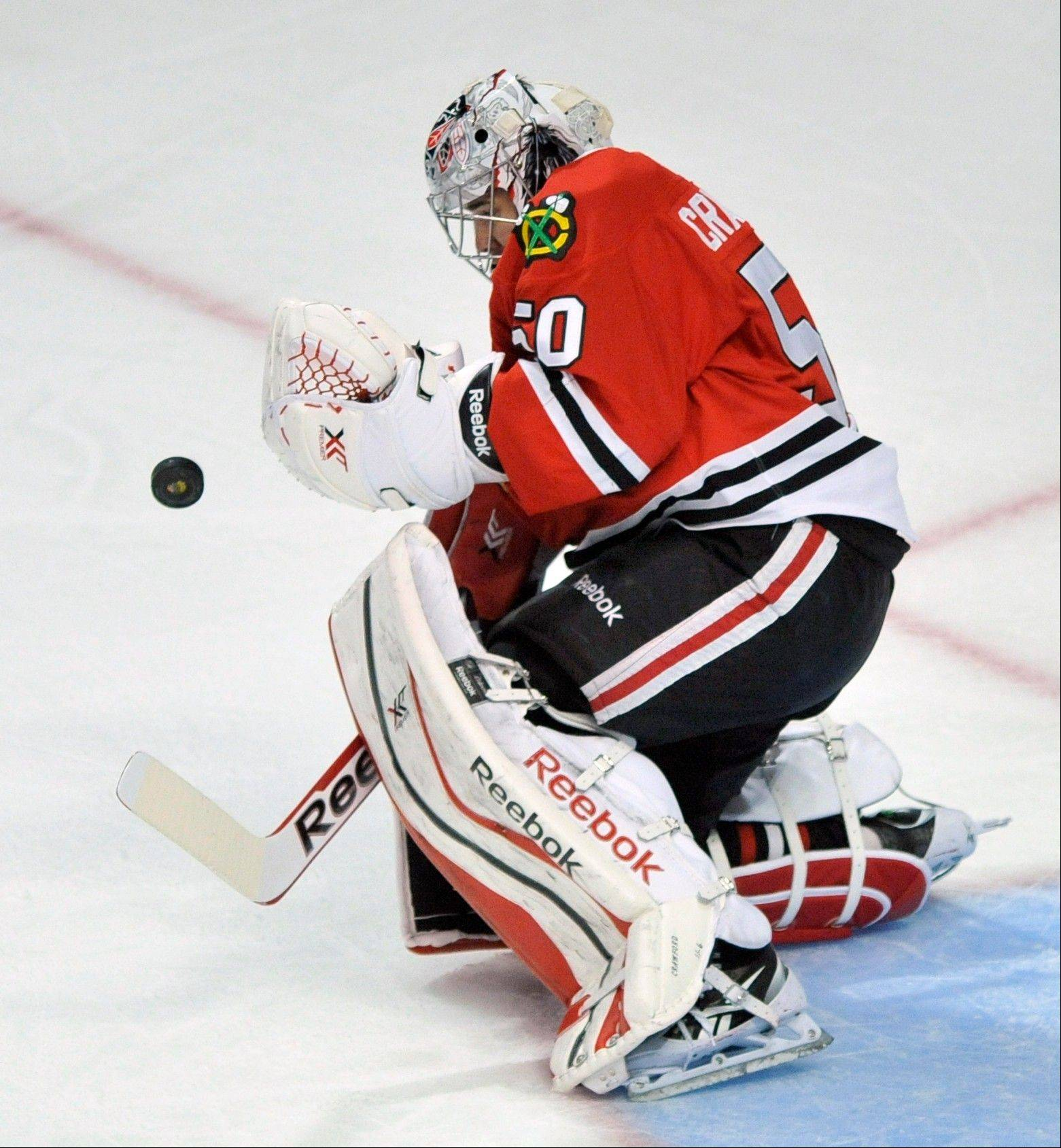 Chicago Blackhawks goalie Corey Crawford makes a save during the third period of an NHL hockey game against the San Jose Sharks in Chicago, Sunday, Jan., 5, 2014. San Jose won 3-2 in a shootout. (AP Photo/Paul Beaty)