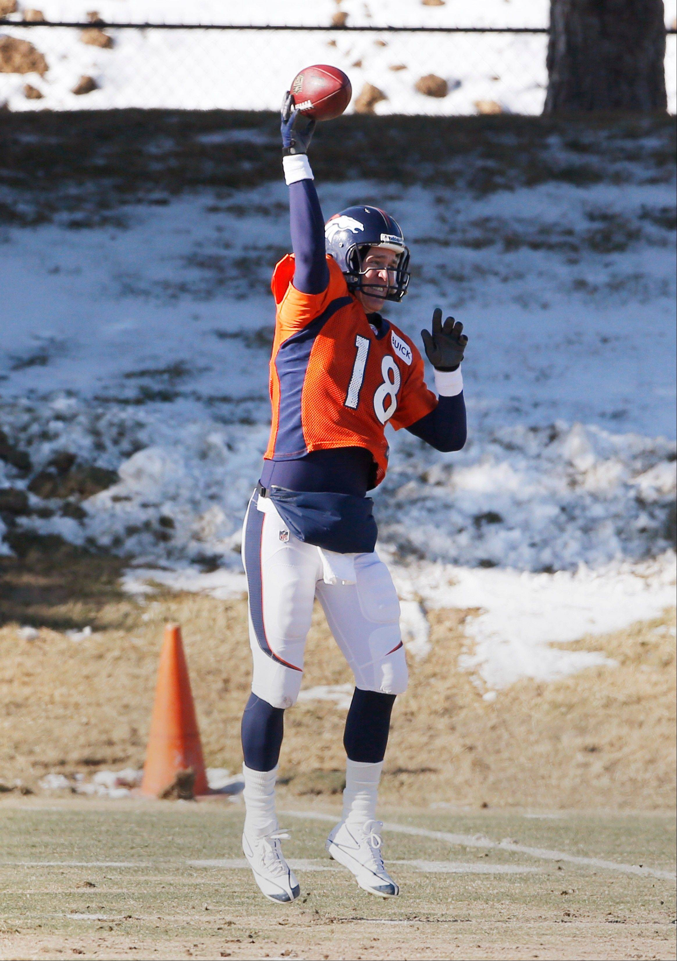 Denver Broncos quarterback Peyton Manning (18) throws a pass at practice for the football team's NFL playoff game against the San Diego Chargers at the Broncos training facility in Englewood, Colo., on Wednesday, Jan. 8, 2014. (AP Photo/Ed Andrieski)