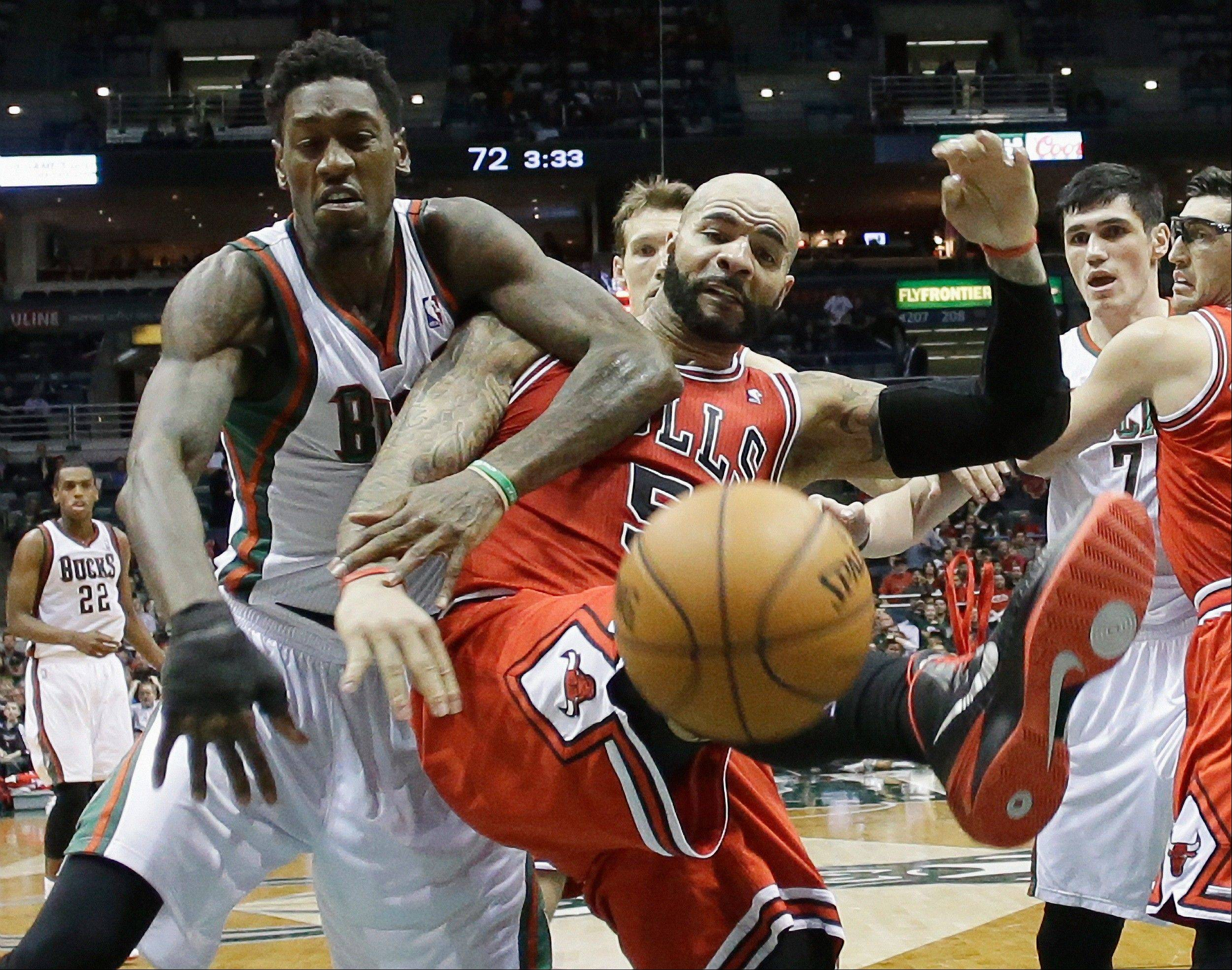 Milwaukee Bucks' Larry Sanders and Chicago Bulls' Carlos Boozer (5) go after a loose ball during the second half of an NBA basketball game Friday, Jan. 10, 2014, in Milwaukee. The Bulls won 81-72. (AP Photo/Morry Gash)