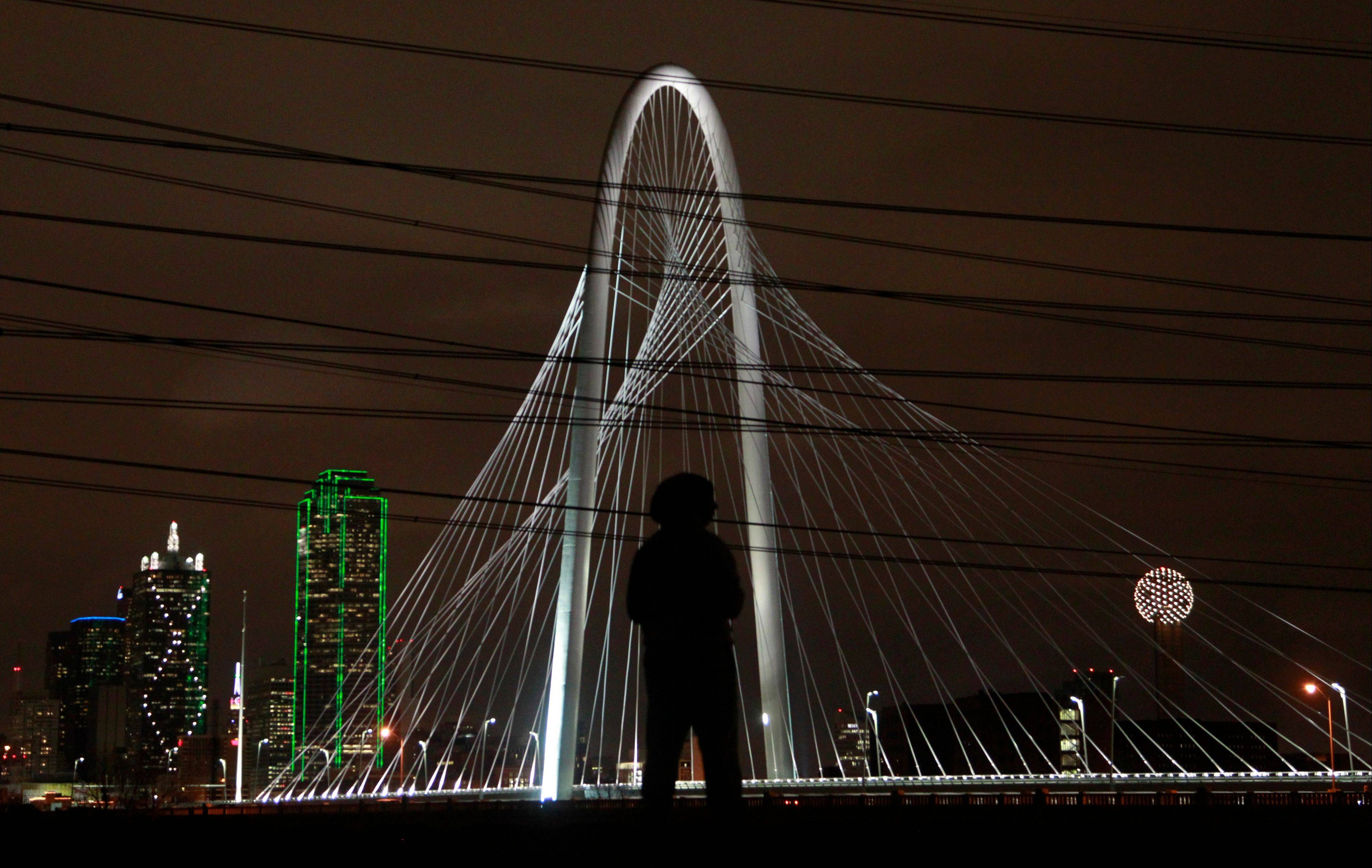 Marcos Carrillo takes a picture of they Margaret Hunt Hill Bridge, which opened in 2012, as it is lit up against the downtown Dallas skyline.
