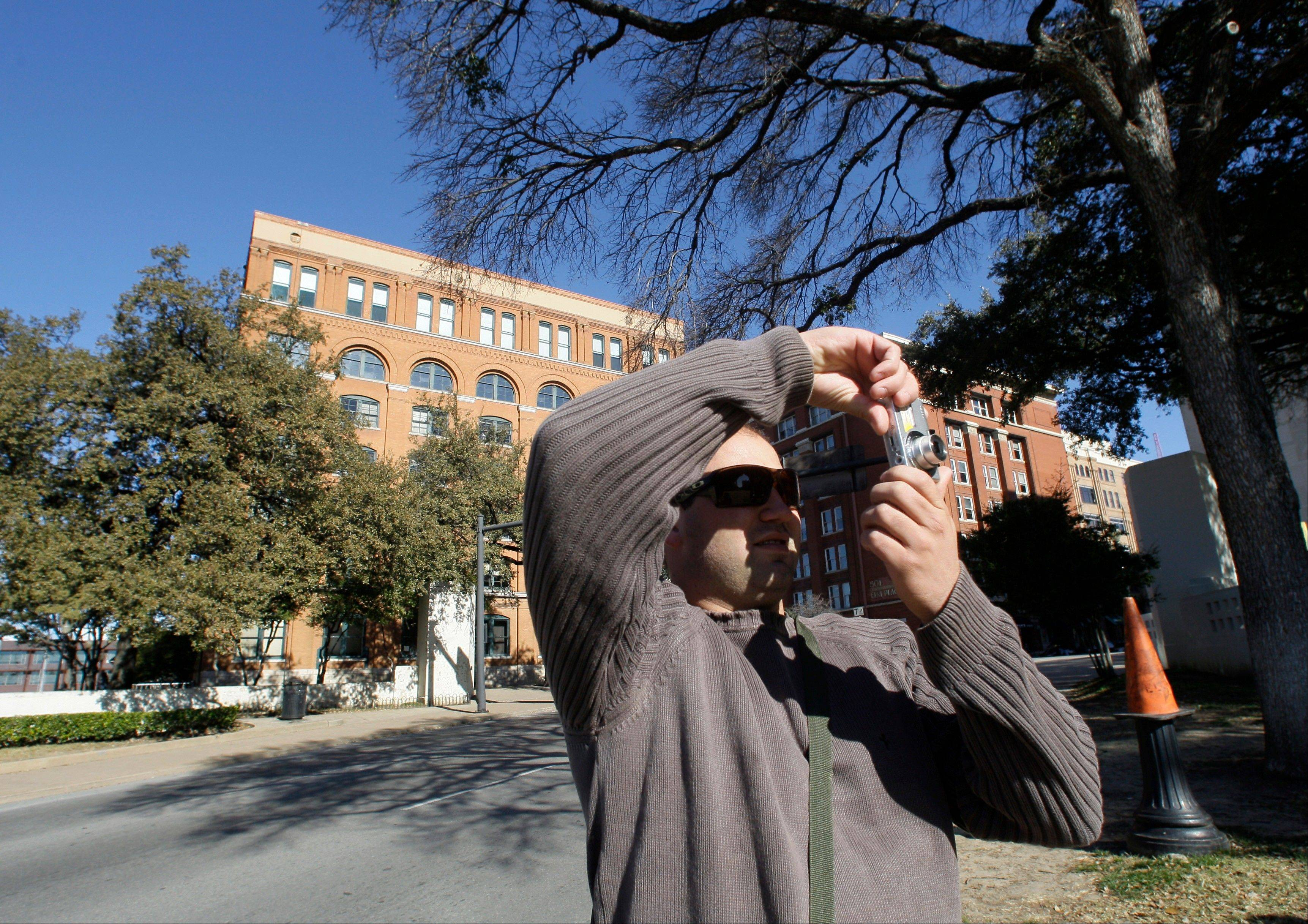 Rafael Boff of Brazil takes photographs while visiting Dealey Plaza, site of President John F. Kennedy's assassination, in Dallas. The building once used as a book depository and now home to the Sixth Floor Museum can be seen in the background.