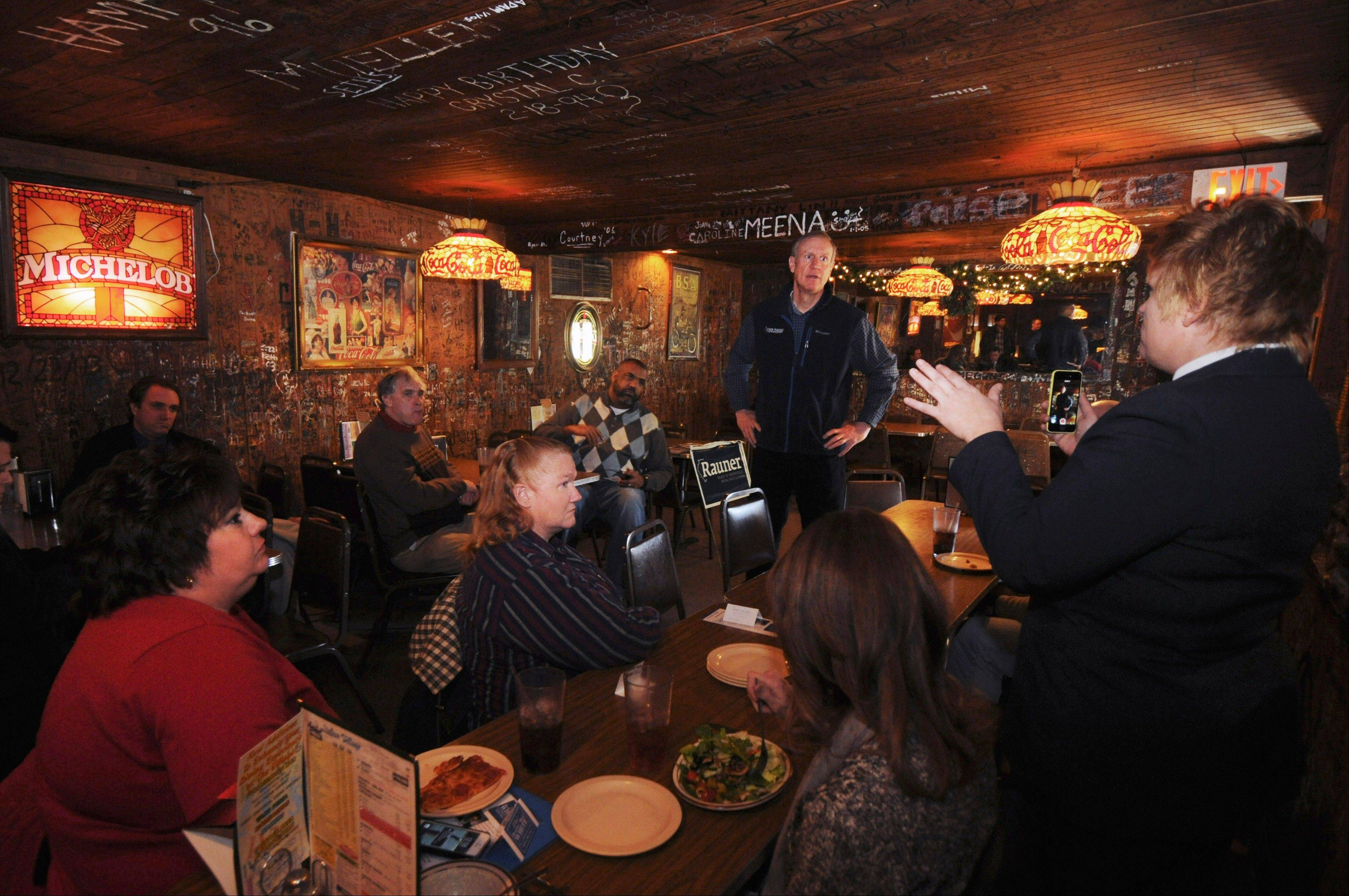 Republican gubernatorial candidate Bruce Rauner listens to comments from guests Tuesday at the Italian Village restaurant in Carbondale, Ill.