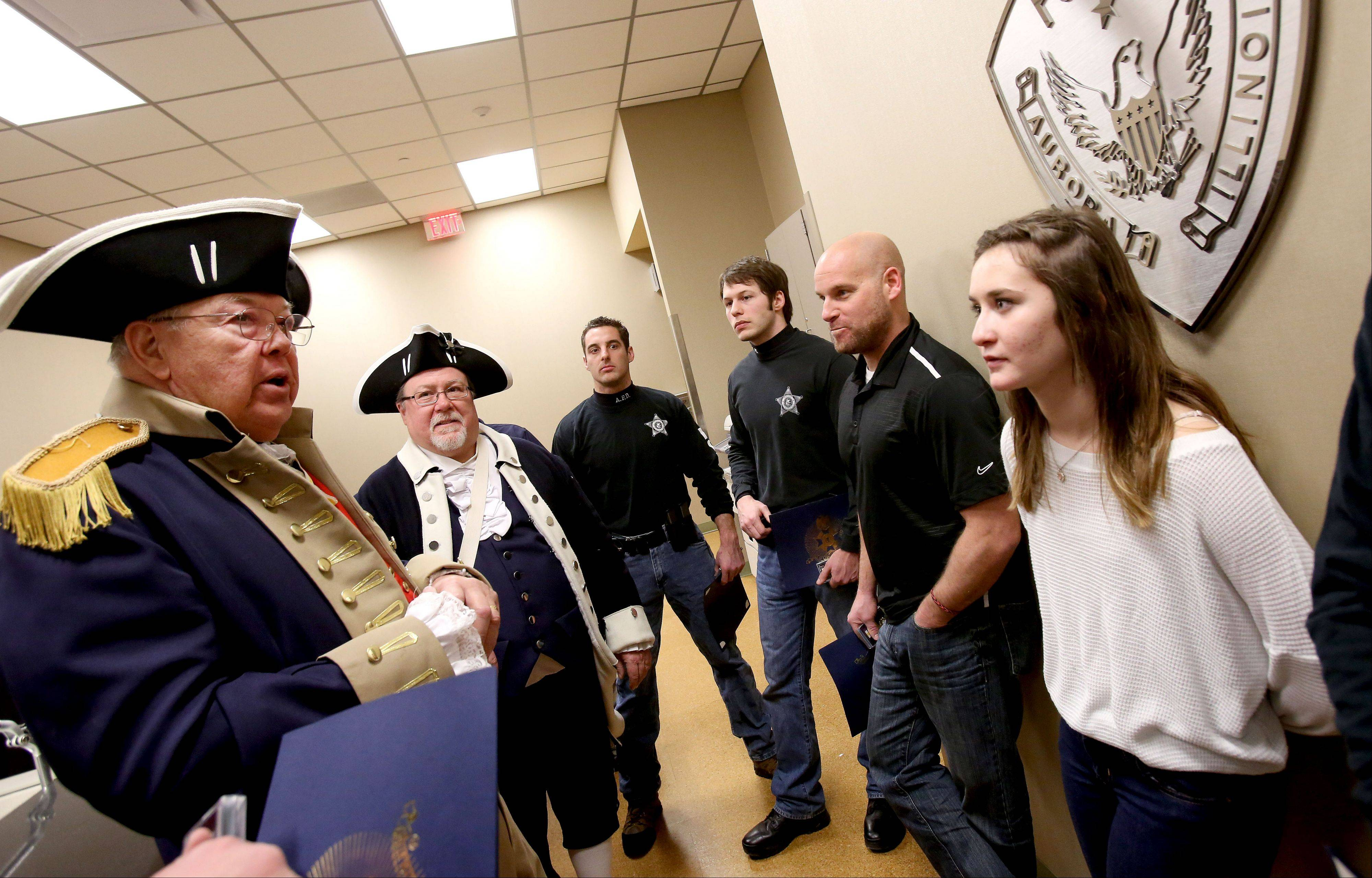 Rod Herbig, left, president of the Fox Valley Chapter of the Sons of the American Revolution, and member Mike Campagnolo talk to Aurora police officers and Annie Prosser, 15, who the officers saved last March from a car that had plunged into a frigid pond.
