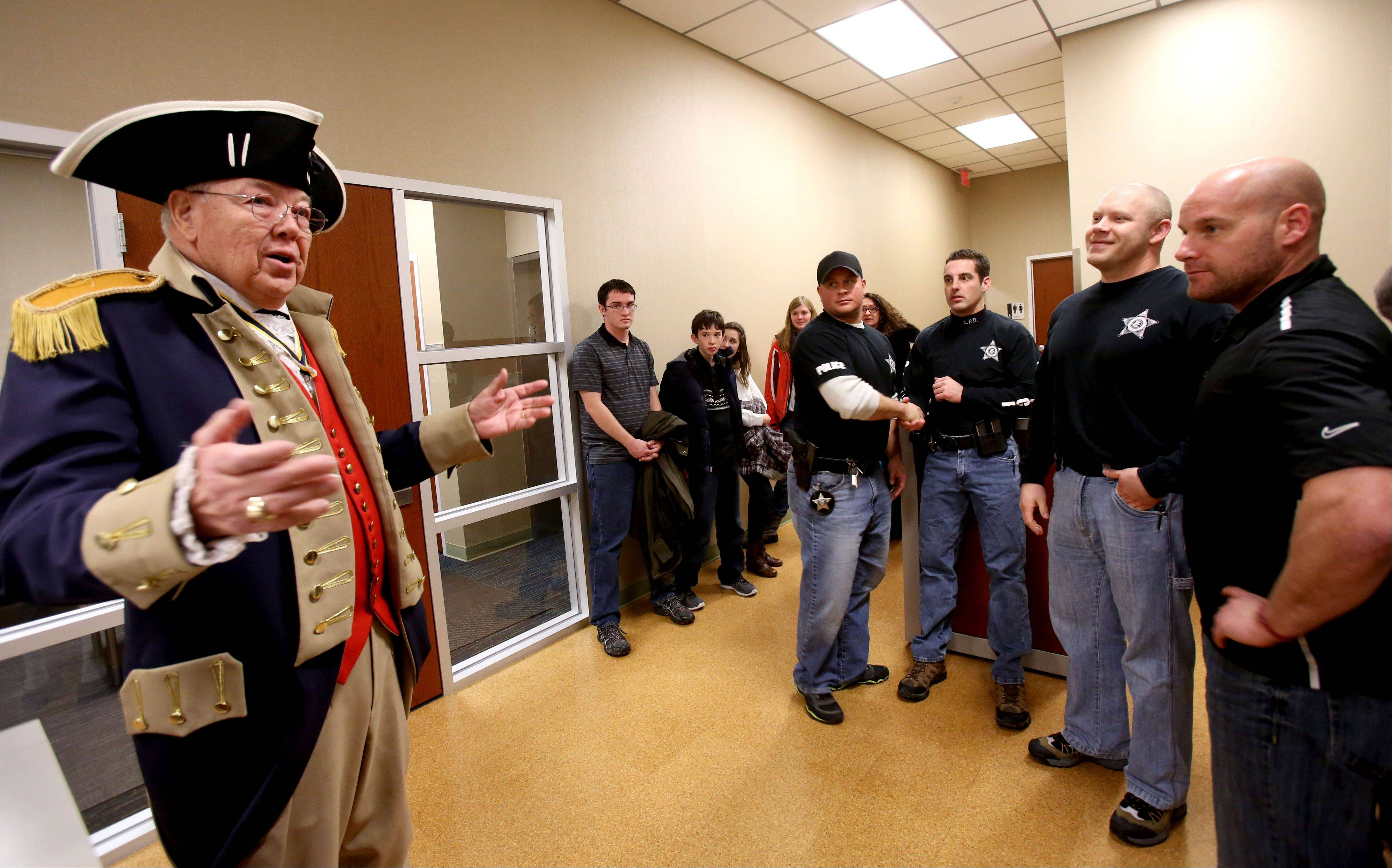 Rod Herbig, left, president of the Fox Valley Chapter of the Sons of the American Revolution, talks to Aurora police officers who saved a Batavia girl last March when the car in which she was riding plunged into a frigid pond. The officers included, from left, Nicholas Gartner, Erik Swastek, W. Joshua Sullivan and Jeffrey Hahn.