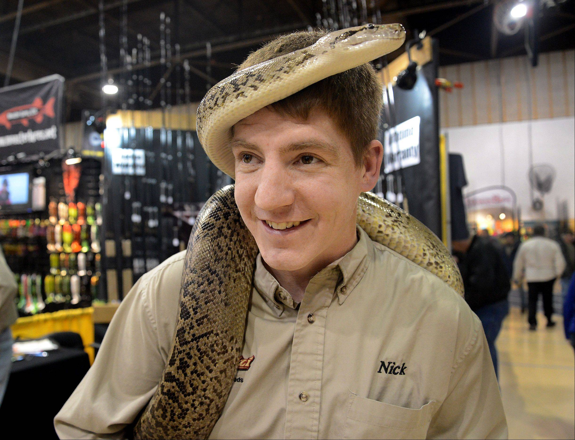 Nick D'Andrea of Chicago gets wrapped up in his granite Burmese python while promoting Migizi snakeskin inlay fishing rods at the Chicago Muskie Show at Harper College.