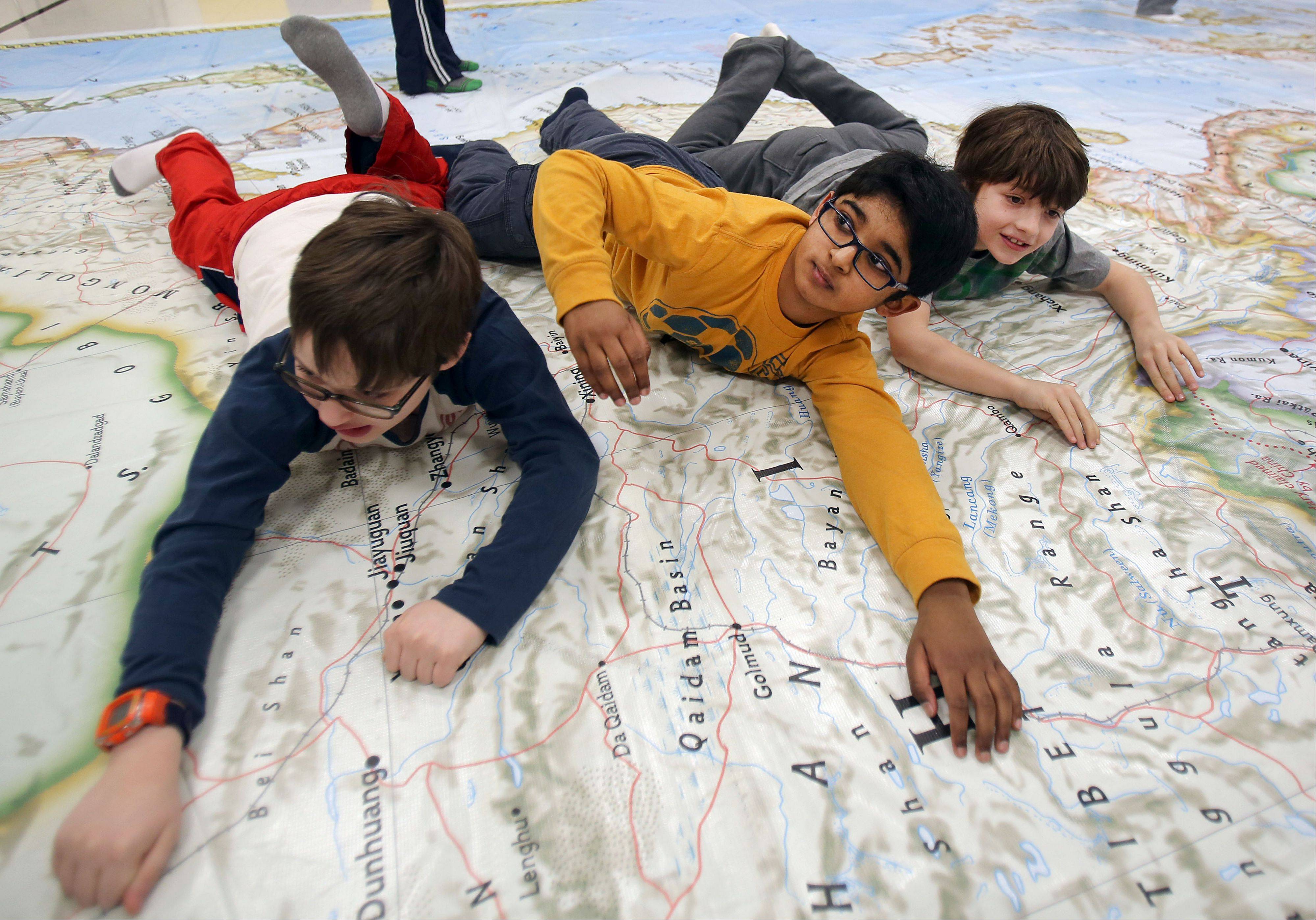 Third-graders Mario Babbo, left, Narayan Manthena and Max Poretto pose for a picture while exploring a giant map of Asia at Half Day School in Lincolnshire Friday. It is part of National Geographic's Giant Traveling Maps program and will remain at the school until Jan. 17.
