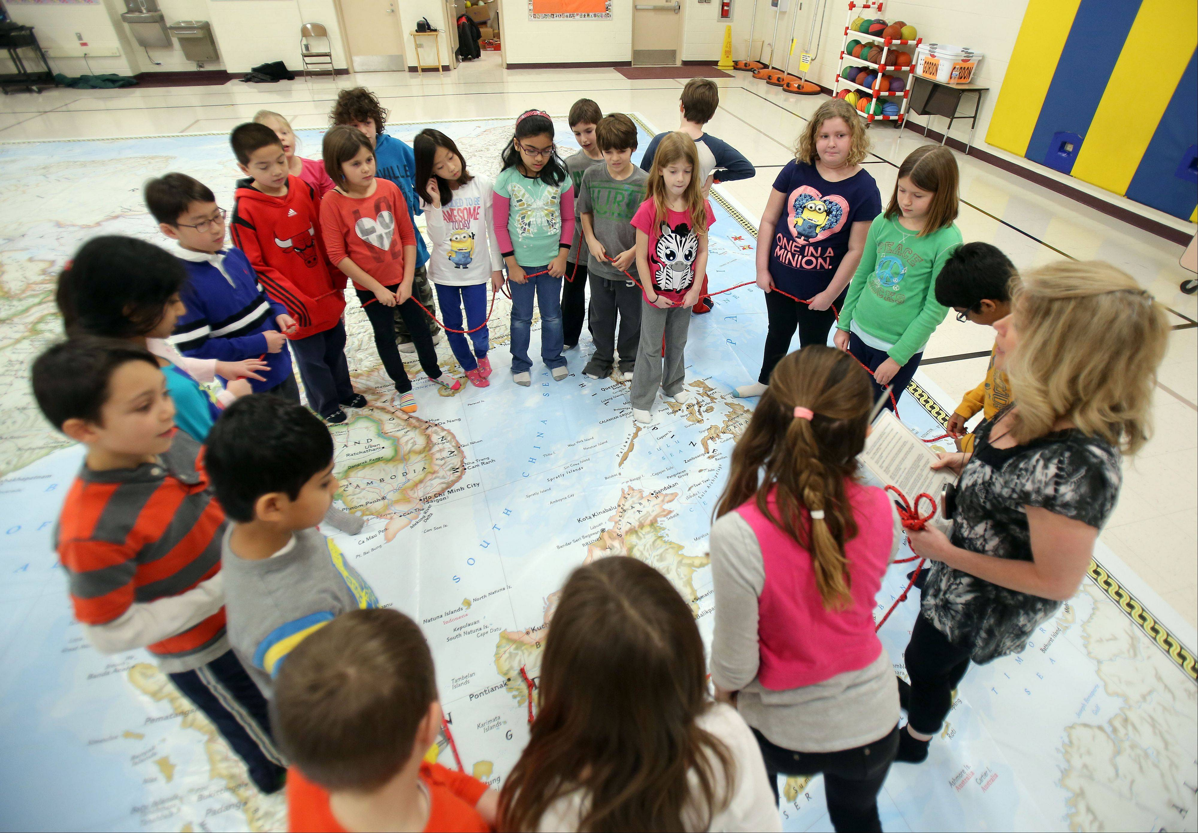 Sharyn Powell's third grade class explored a giant map of Asia at Half Day School in Lincolnshire on Friday. The map measures 26 feet by 35 feet.