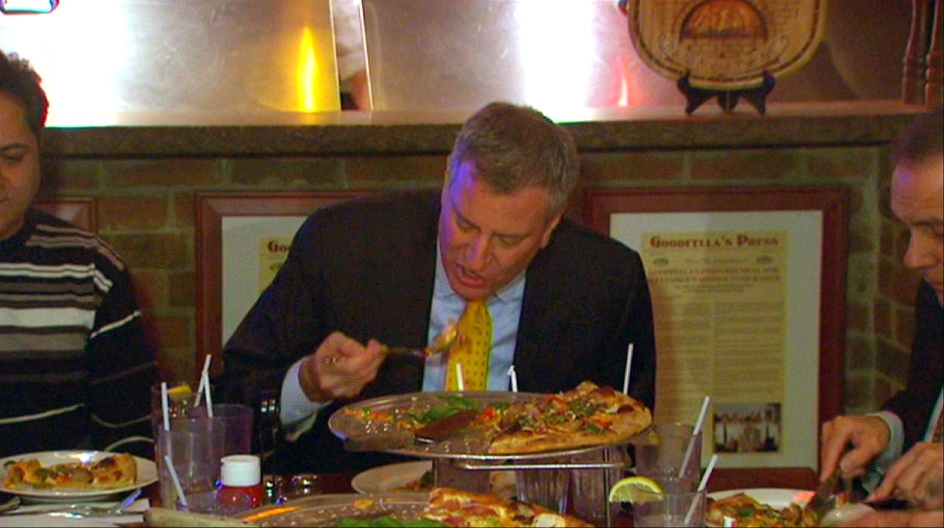 New York Mayor Bill de Blasio eats pizza with a fork Friday at Goodfellas Pizza in the Staten Island borough of New York.