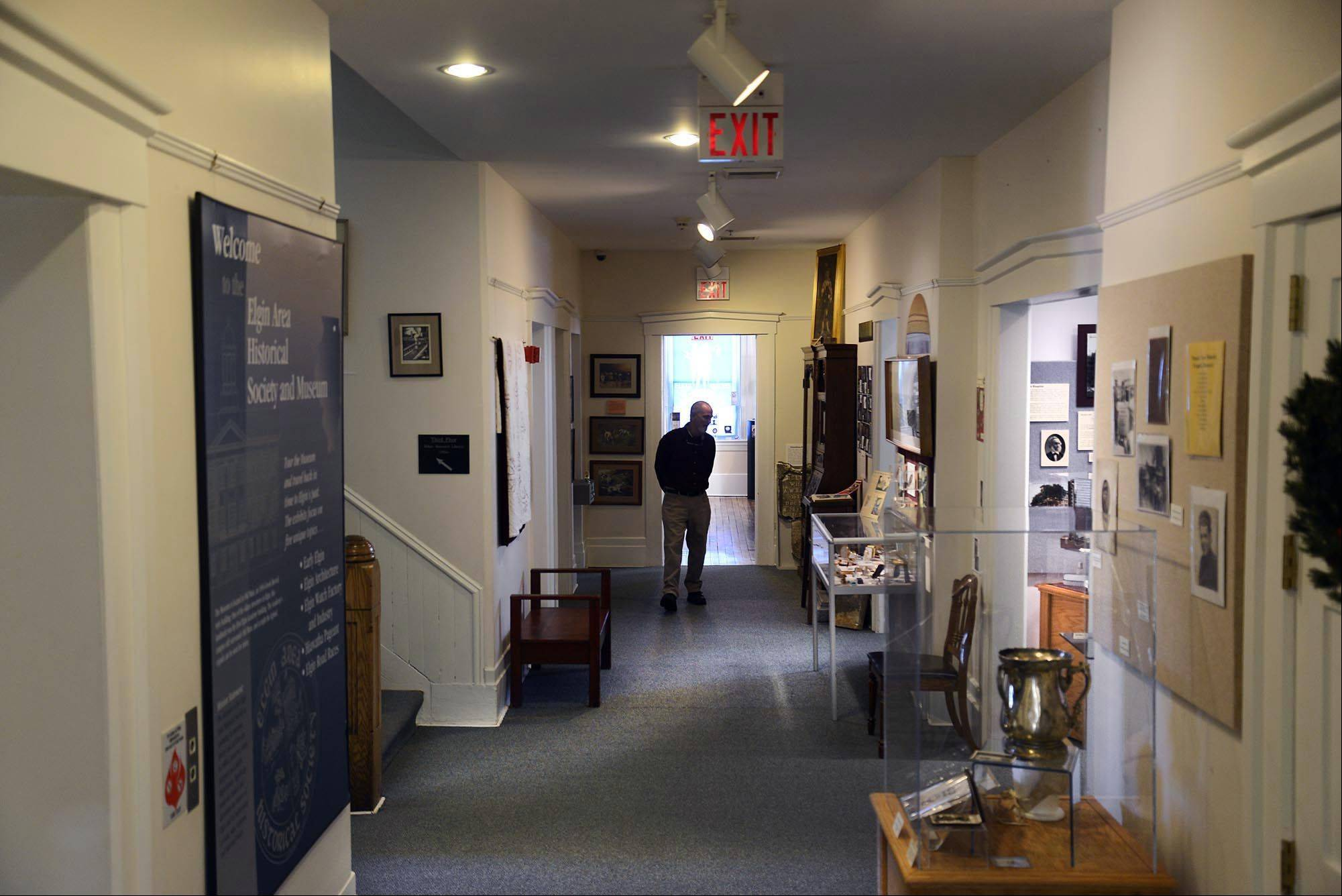 George Rowe stands in a second floor hallway of the Elgin History Museum. As president of the Elgin Area Historical Society, it is his job to keep control of the 159-year-old landmark museum on the campus of Elgin Academy. The museum was built in 1855 and was the first high school in Illinois. It now houses more than 10,000 Elgin historical artifacts.