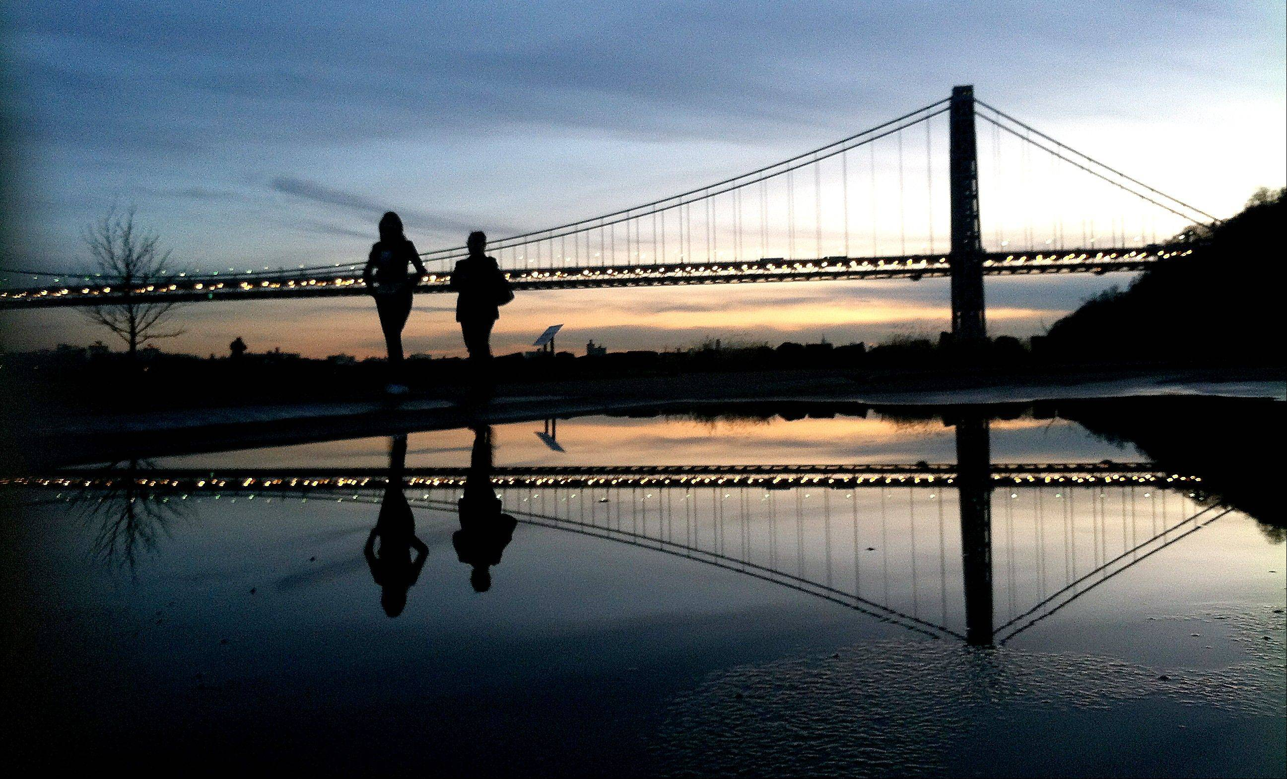 Two women walk at Palisades Interstate Park as the sun sets over the George Washington Bridge, in Fort Lee, N.J. Many people have known little about Fort Lee until a political scandal centering on New Jersey Gov. Chris Christie enveloped the borough.