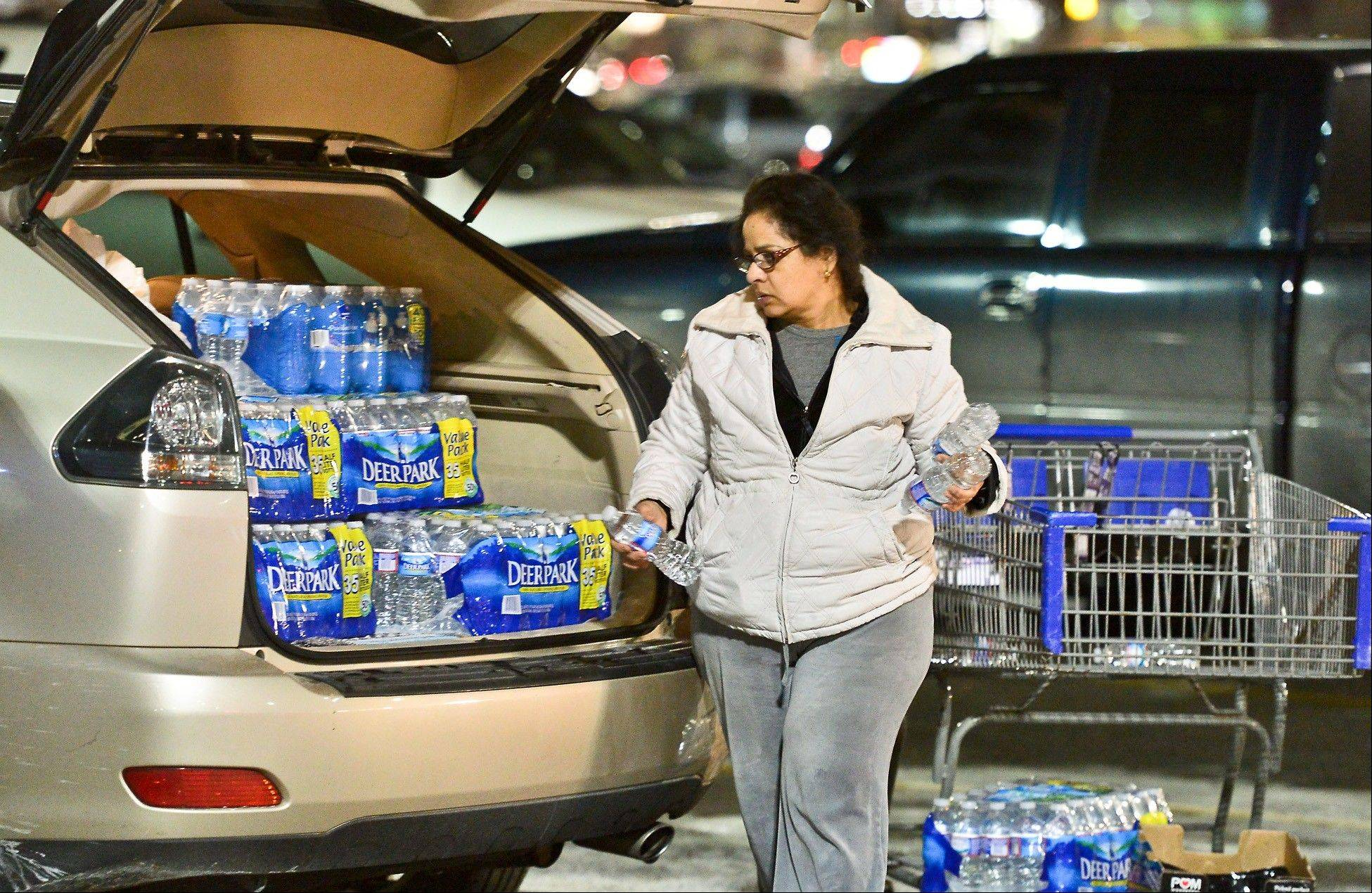 Charleston resident Niru Parikshak loads up the back of her car with bottled water Thursday Jan. 9, 2014 in Charleston, W.Va. Every retailer for a 20-mile radius sold out of bottled water after a chemical leak Thursday morning up river from the WV American Plant on the Elk River forced the water plant to shut down.