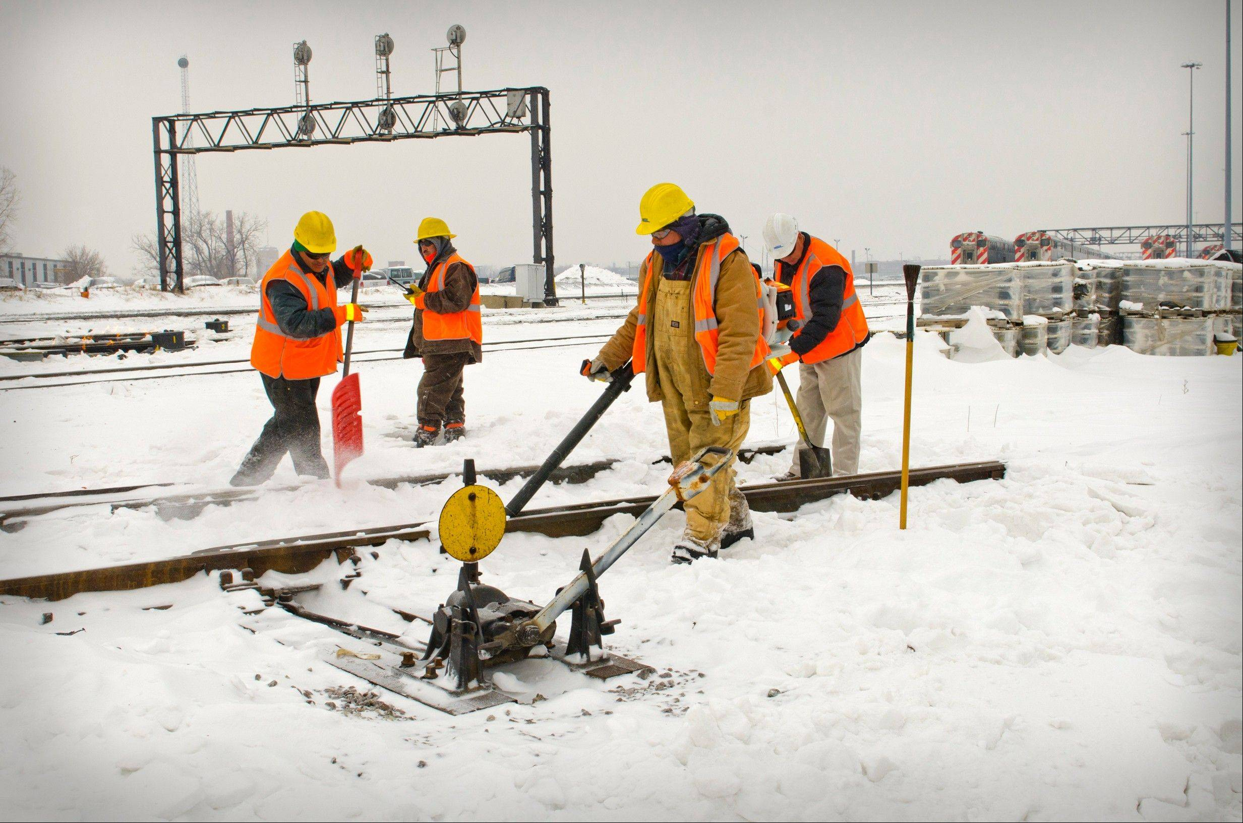 Photo by Ron Wojkovich, courtesy of MetraMetra crews get rid of ice and snow on a signal Thursday.