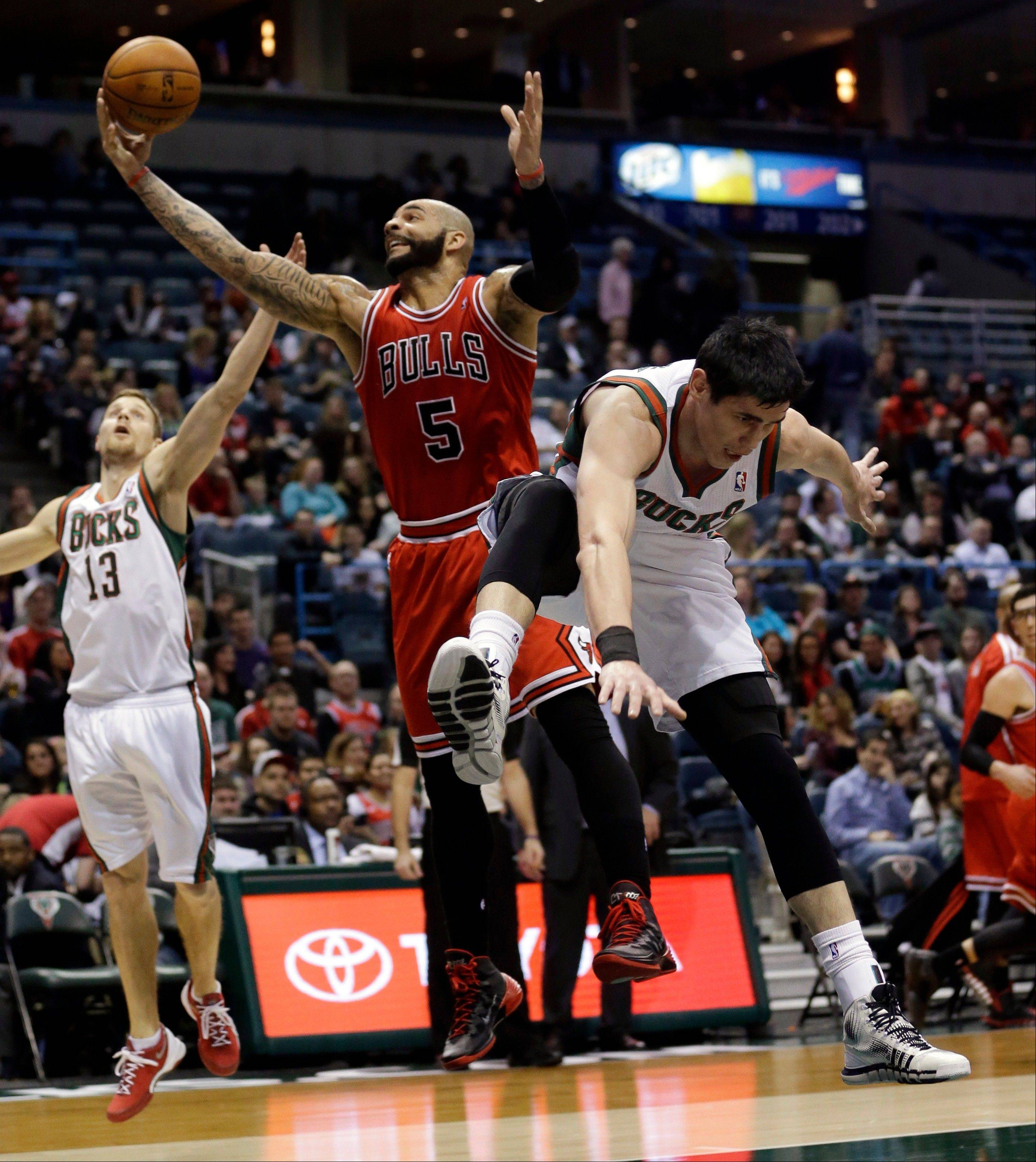 Chicago Bulls' Carlos Boozer (5) goes after a rebound between Milwaukee Bucks' Ersan Ilyasova and Luke Ridnour (13) during the first half of an NBA basketball game Friday, Jan. 10, 2014, in Milwaukee.