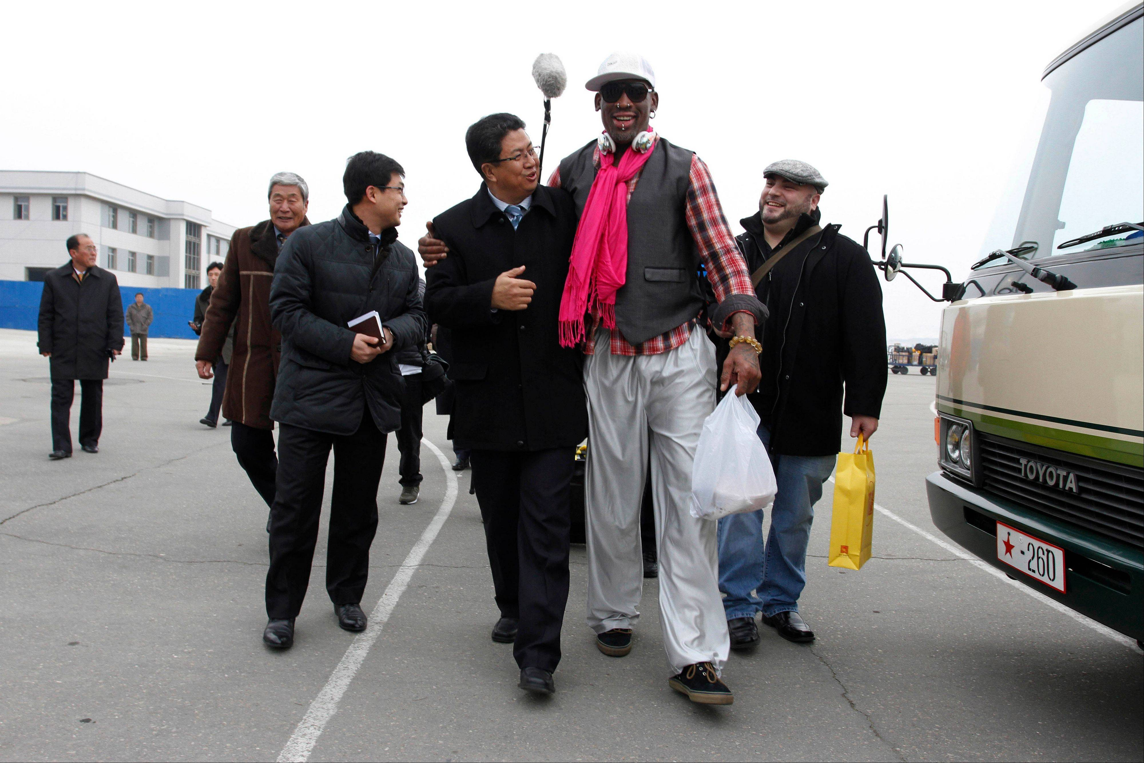 AP10ThingsToSee - Former NBA basketball star Dennis Rodman, second right, walks with North Korea's Sports Ministry Vice Minister Son Kwang Ho, third right, upon his arrival at the international airport in Pyongyang, North Korea, Monday, Jan. 6, 2014. Rodman took a team of former NBA players on a trip for an exhibition game on Kim Jong Un's birthday, Wednesday, Jan. 8.