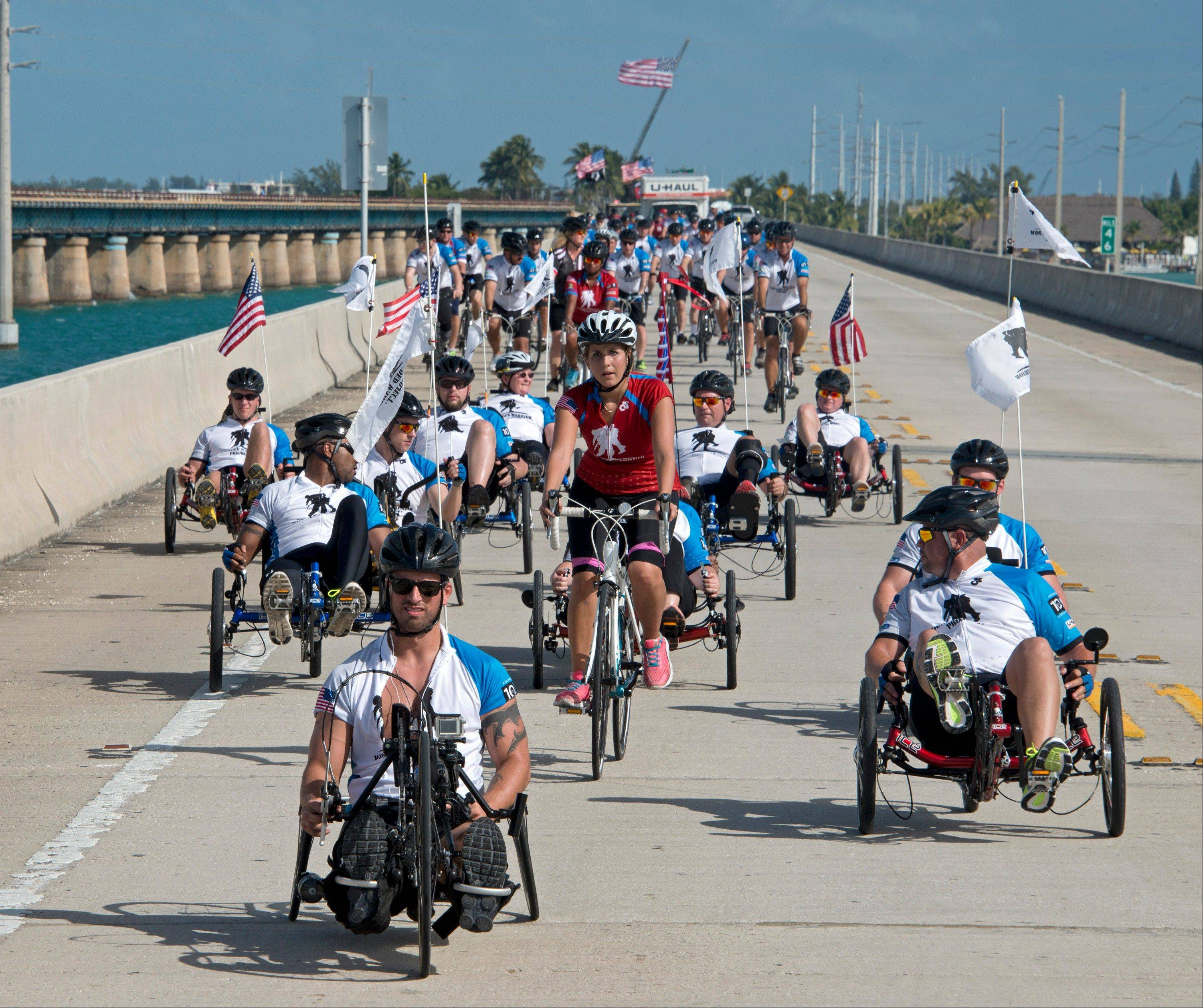 Wounded veterans of wars in Iraq and Afghanistan pedal their way Friday across the Seven Mile Bridge in the Florida Keys near Marathon, Fla.